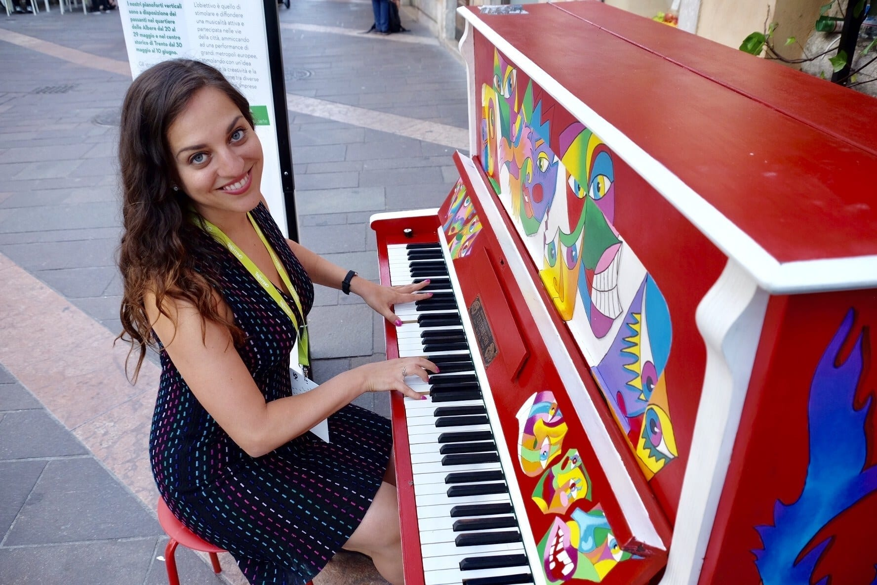 Kate is sitting down and playing a bright red painted piano in the streets of Trento. She looks at the camera and smiles.