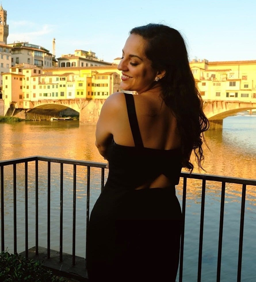 Kate wears a long black sleeveless dress and is facing her body away from the camera but turning back toward it with her face, smiling with her eyes closed. Behind her is the Ponte Vecchio, the old bridge of Florence covered with jewelry stores, bathed in golden light.