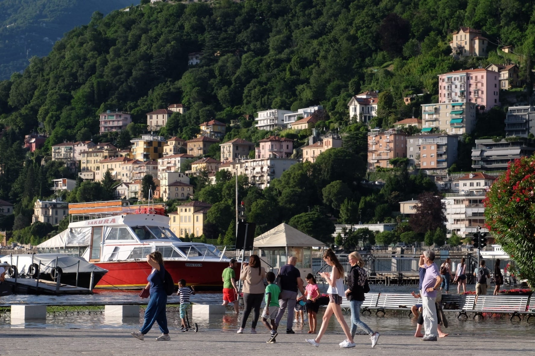 Several people walk across a piazza in Como, Italy. In the background is the lake and several houses built on a green mountainside leading into the lake.