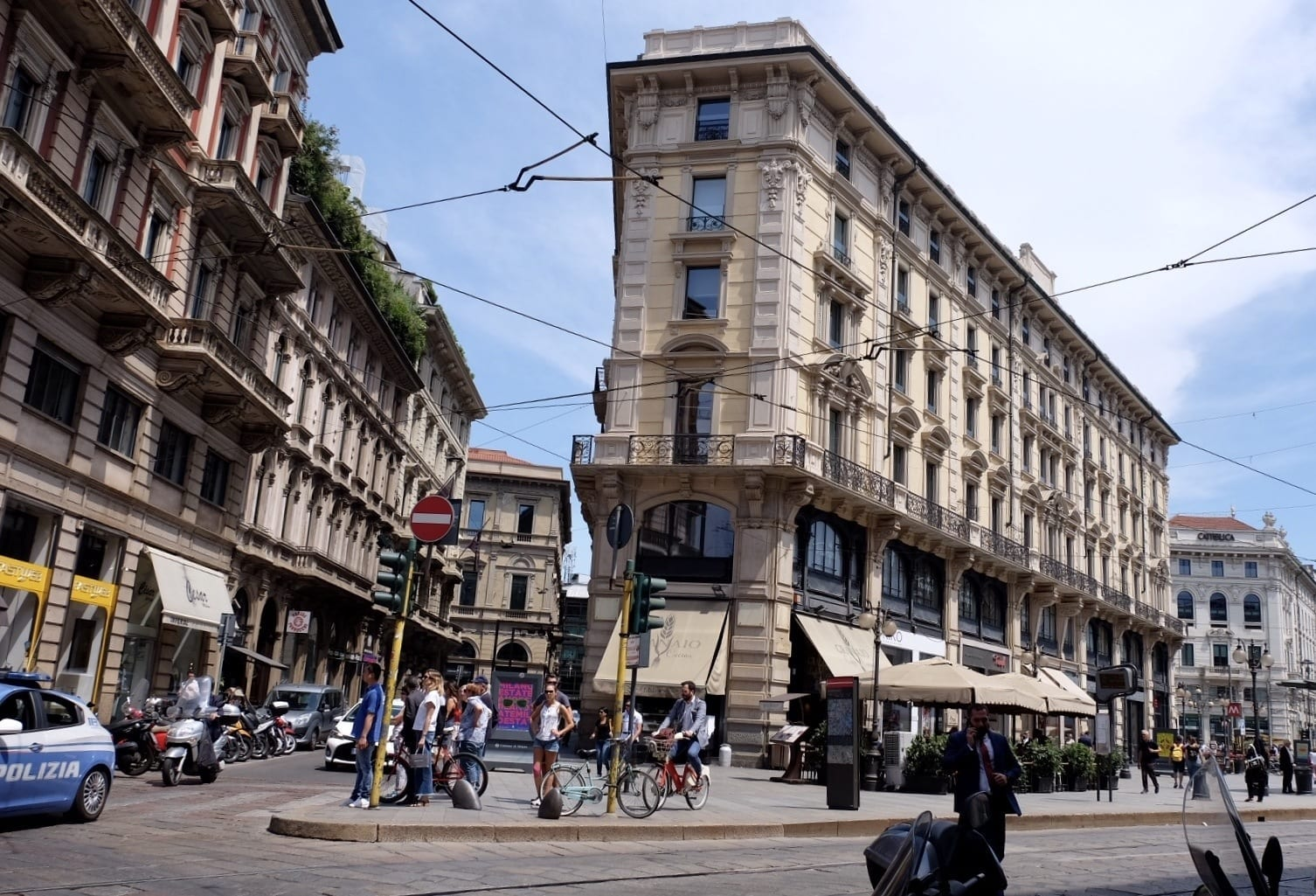 Milan street scene: On a block that juts out triangularly into the street, several people wait for the walk signal at a stoplight. The surrounding buildings are gray with ornate balconies for each window. On the ground floor is a cafe with white awnings.