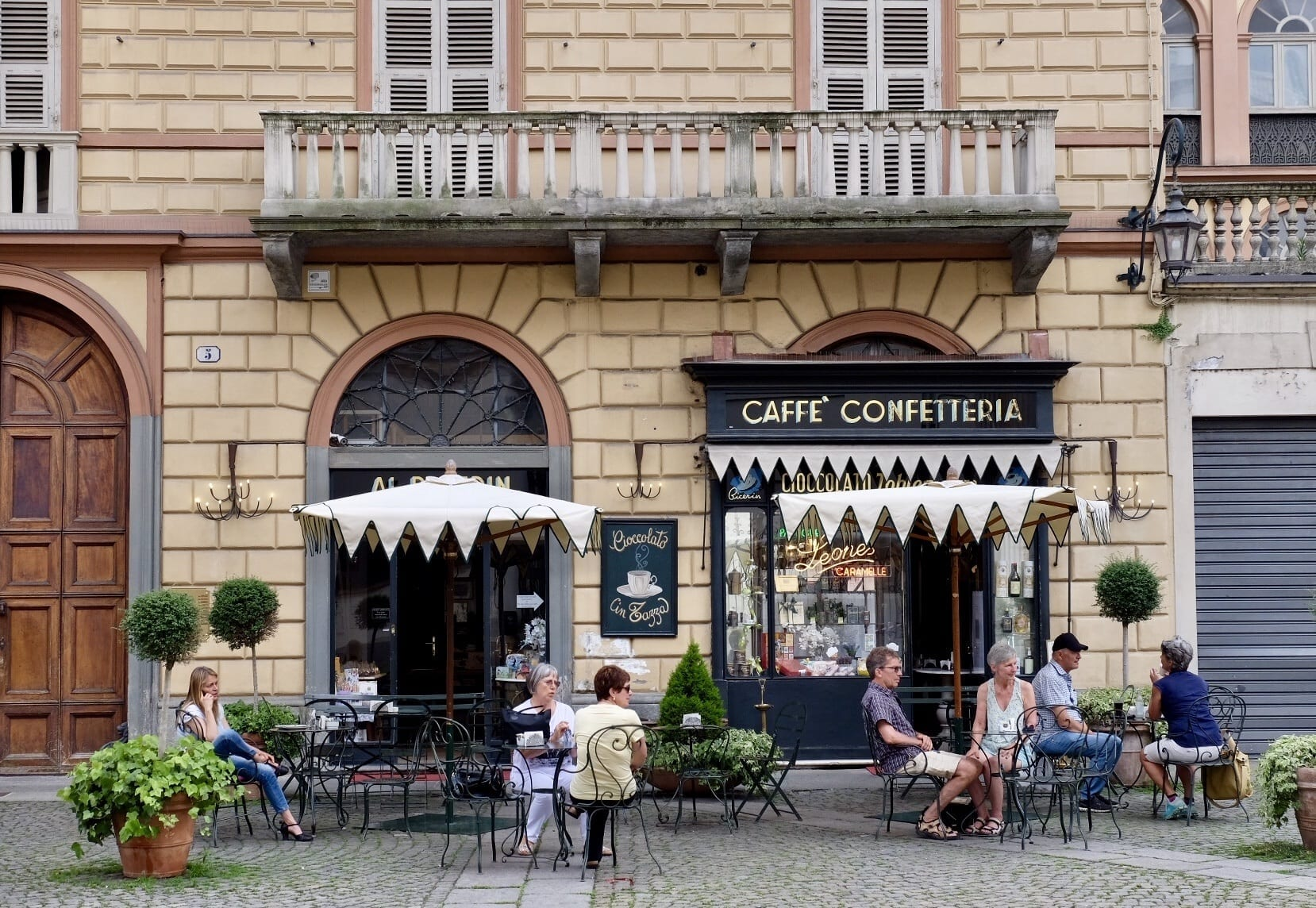 Several people sit at a sidewalk cafe in Torino, Italy. There are umbrellas and the building has a balcony on it.