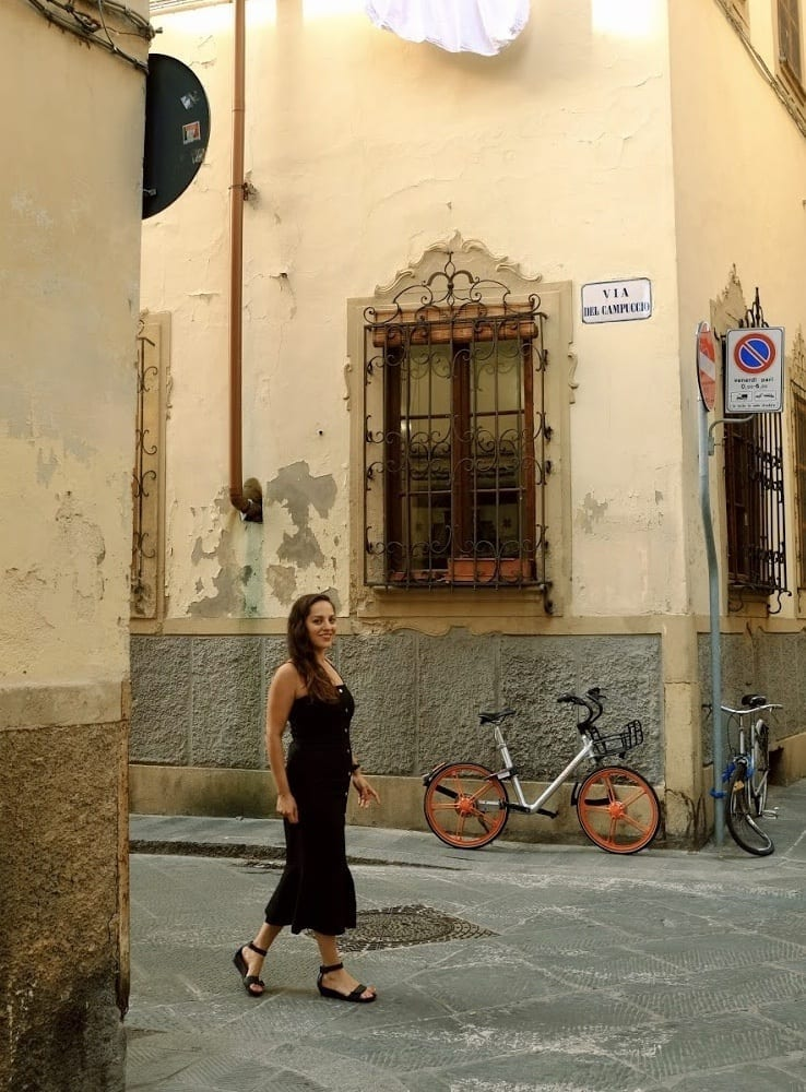 Kate walks down a side street in Florence wearing a long black midi dress with a flared bottom. There is a bike and a wooden window with iron bars on it behind her.