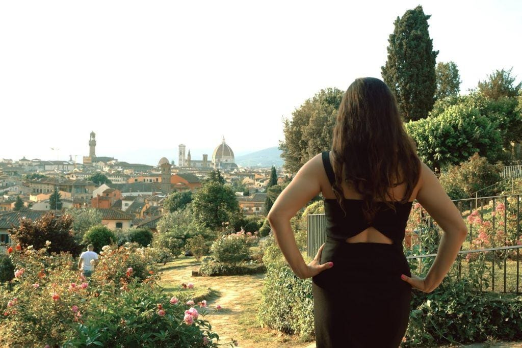 Kate faces away from the camera and stands facing the Duomo in Florence in the distance. She is in a rose garden, surrounded by greenery.