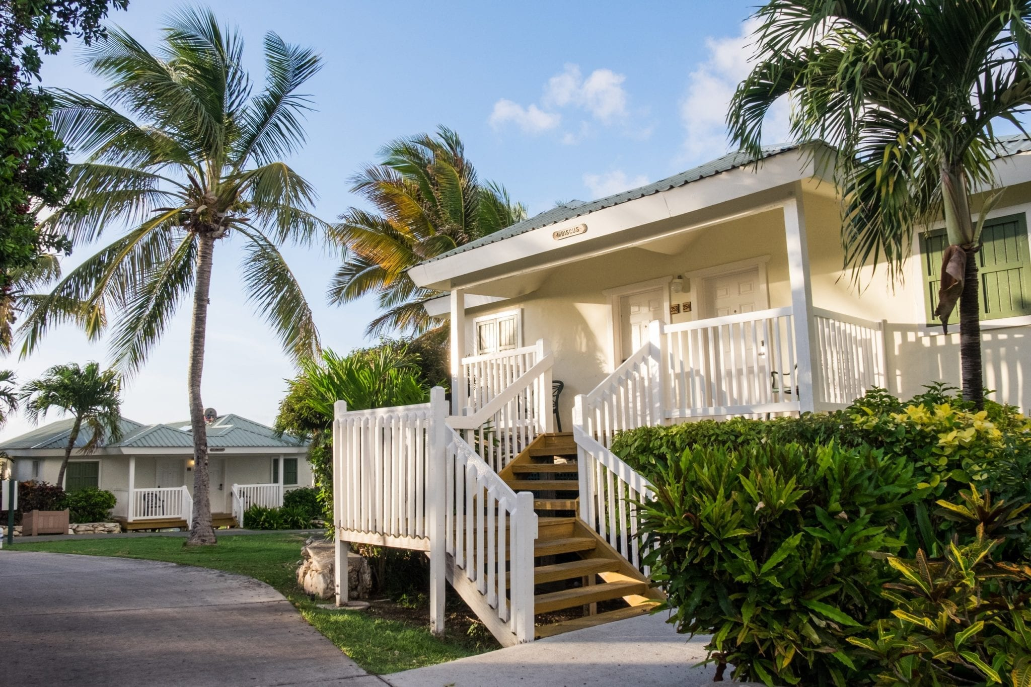 A small White House with picket fencing along the staircase leading upward, surrounded by palm trees underneath a blue sky.