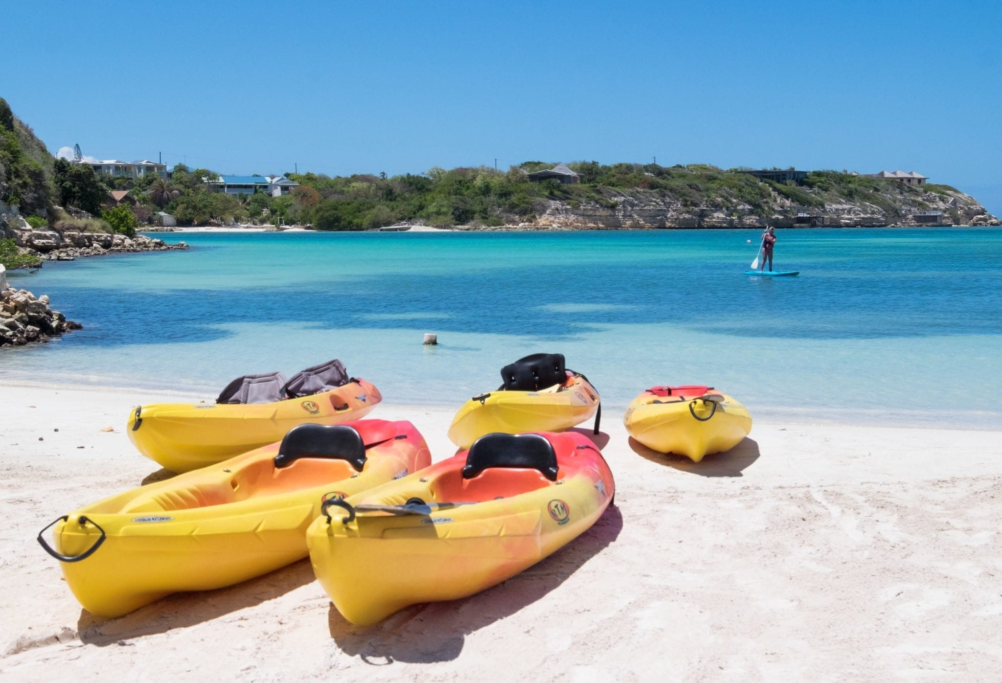 Several yellow and red kayaks resting on a white sand beach in front of a turquoise ocean.