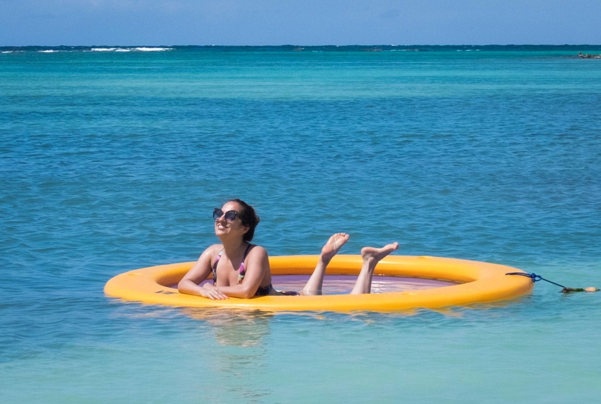"""Kate is in a yellow """"water hammock"""" -- a round hammock-like device in the middle of the turquoise Caribbean Sea underneath a blue sky with a few clouds. Kate is wearing sunglasses and is on her elbows with her legs playfully in the air."""