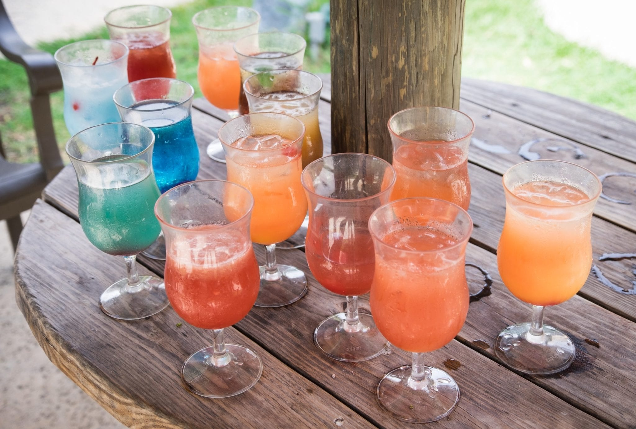 A wooden table topped with 13 various brightly colored cocktails in water goblets, some of them more finished than others.
