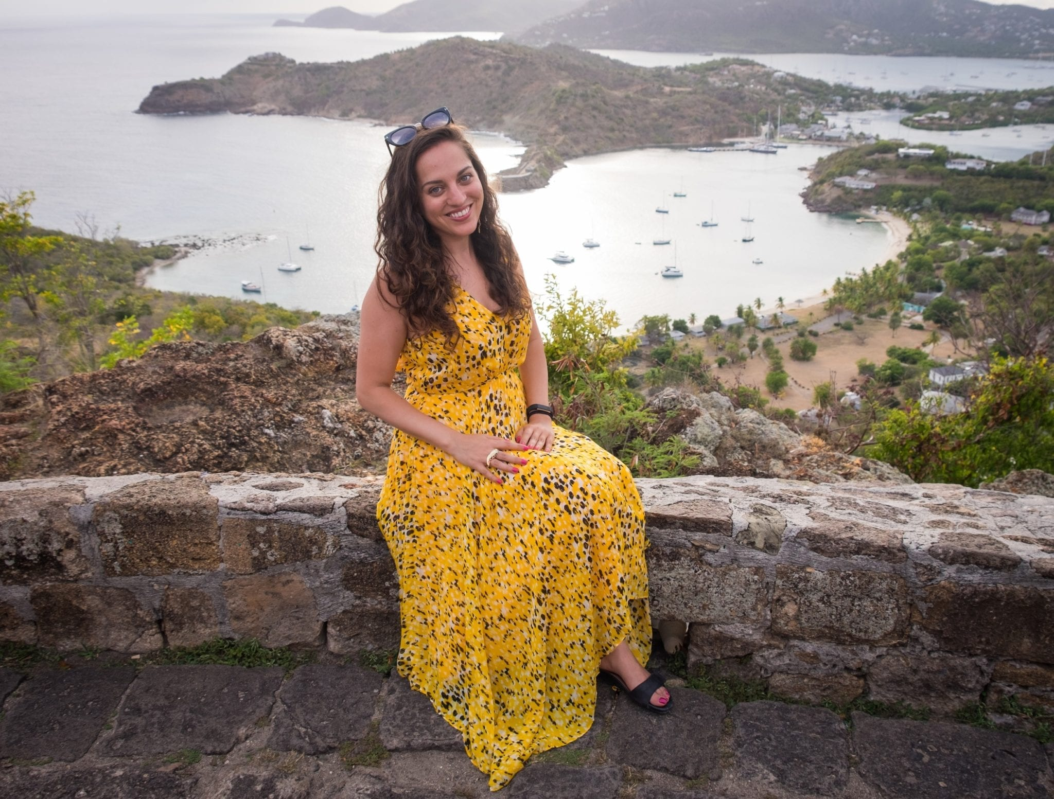 Kate sitting on a short wall in a long gauzy yellow and black gown. In the background is a view over the White Sea down below, and mountains in the distance.