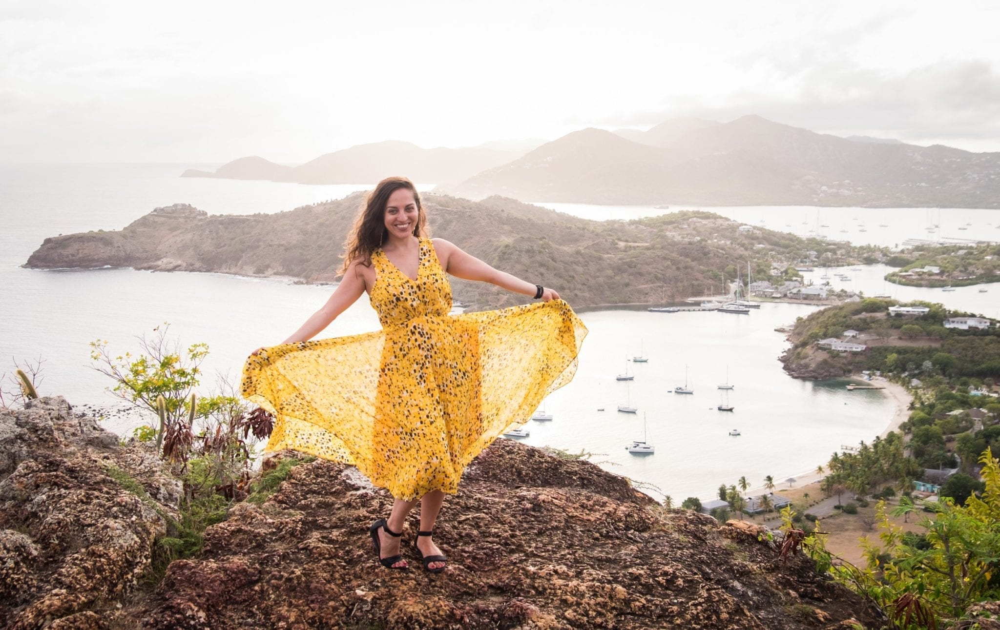 Kate wearing a long yellow and black-spotted gauzy gown over an overlook in Shirley Heights, Antigua. Kate is holding the gauzy outer layer open and smiling. In the background is a view over the White Sea down below, and mountains in the distance.