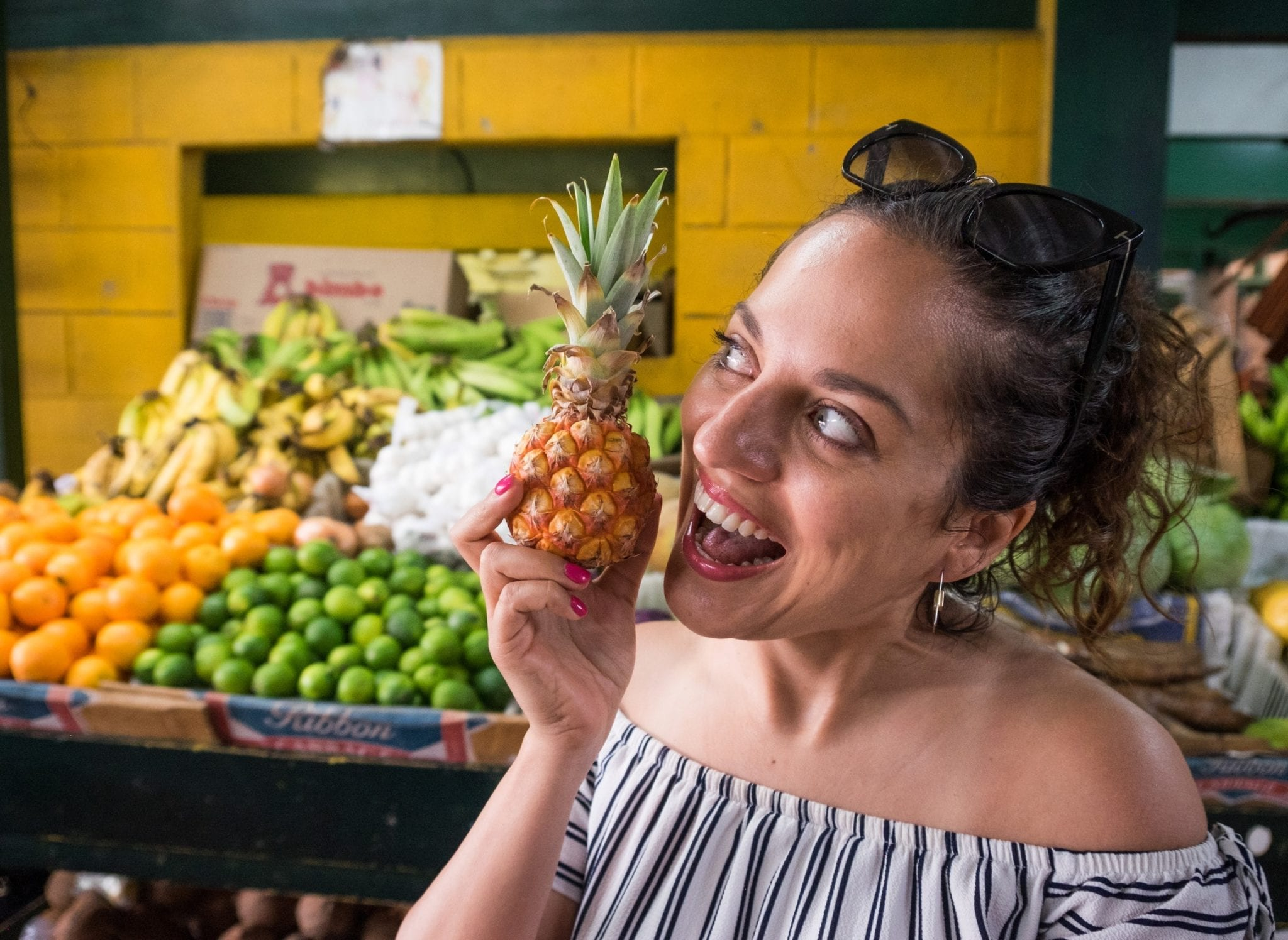 Kate holds a tiny Antigua black pineapple in her hand. It is the size of her fist. She holds it next to her mouth and pretends to eat the whole thing, a smile on her face. In the background are displays of fruit, including limes and oranges.