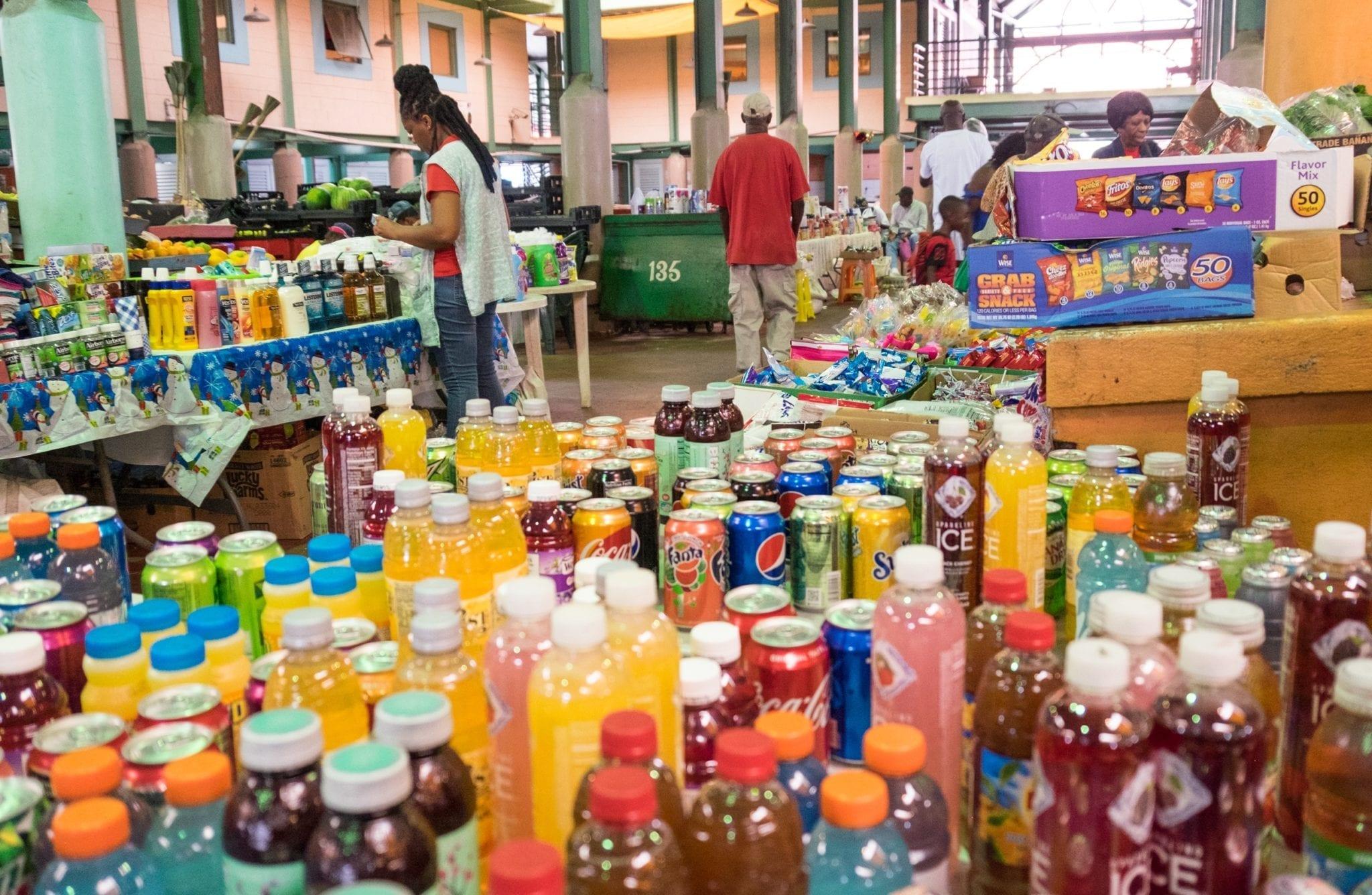 Dozens of bottled drinks on a table in a market in St. John's, Antigua
