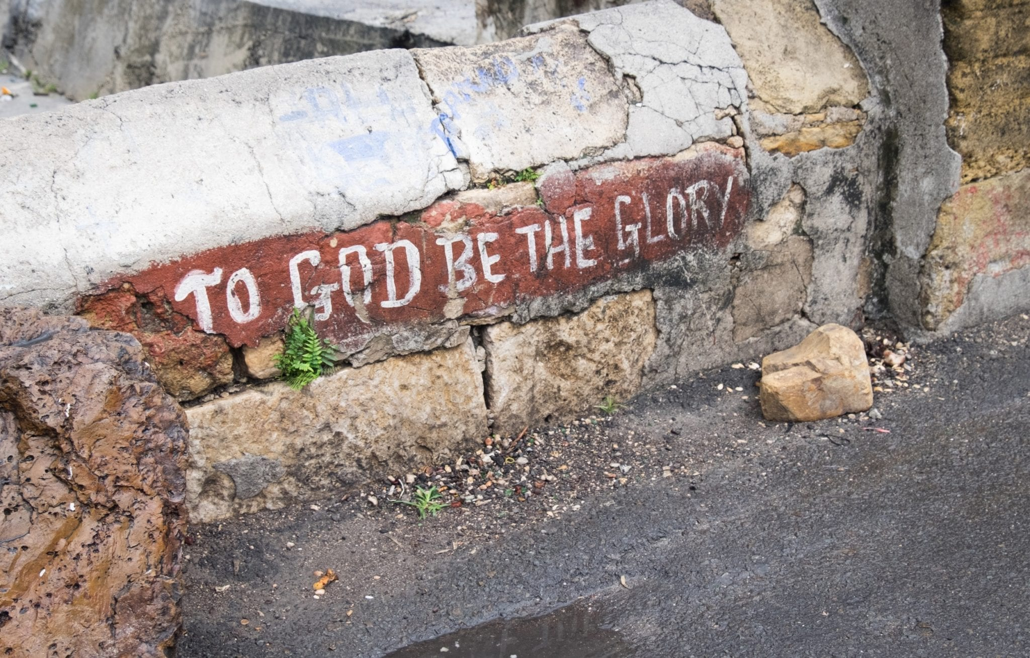 "A cracked wall on a sidewalk reads ""To God Be the Glory"" in St. John's Antigua"