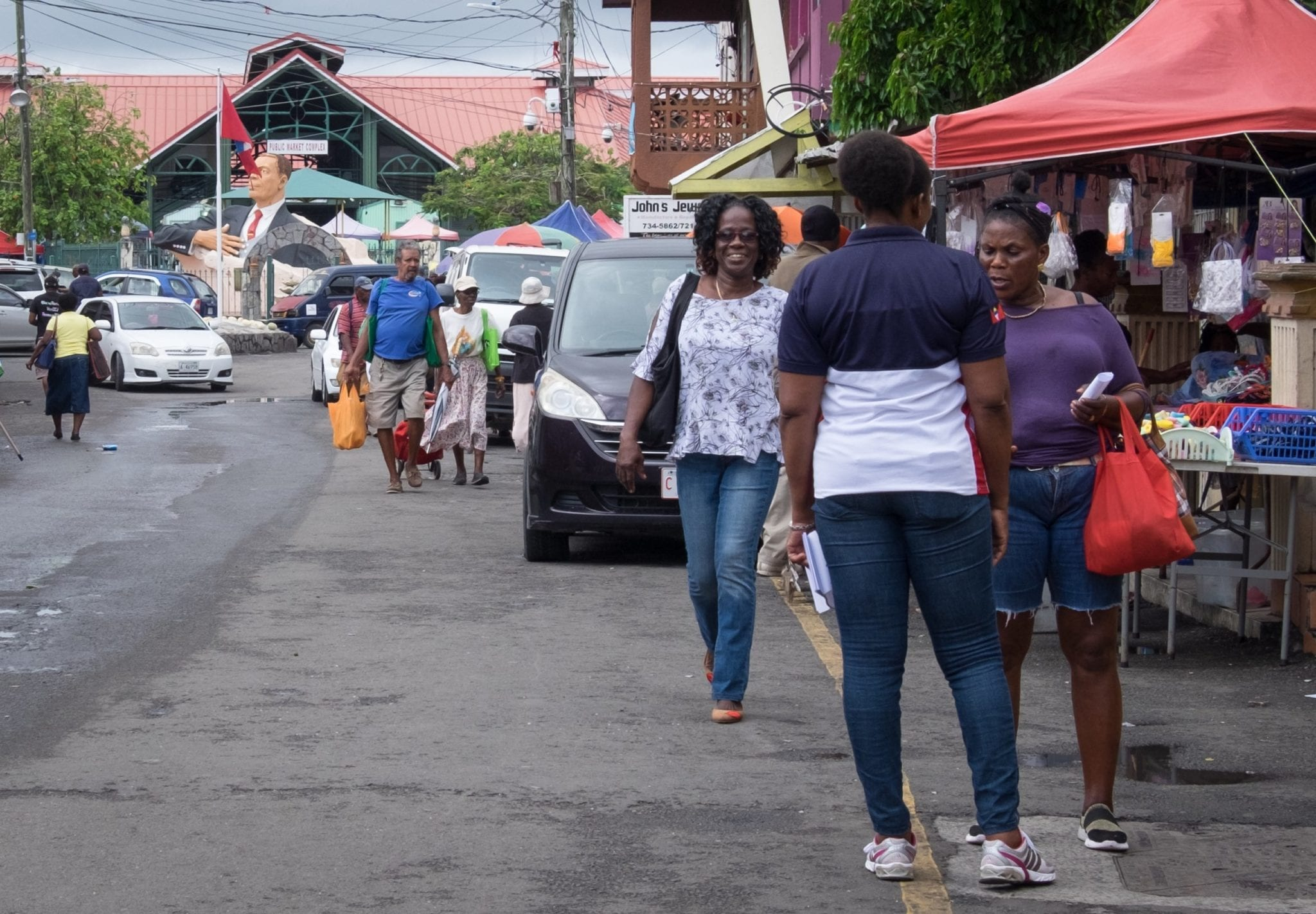 Two women green each other when walking down the street in St. John's Antigua.