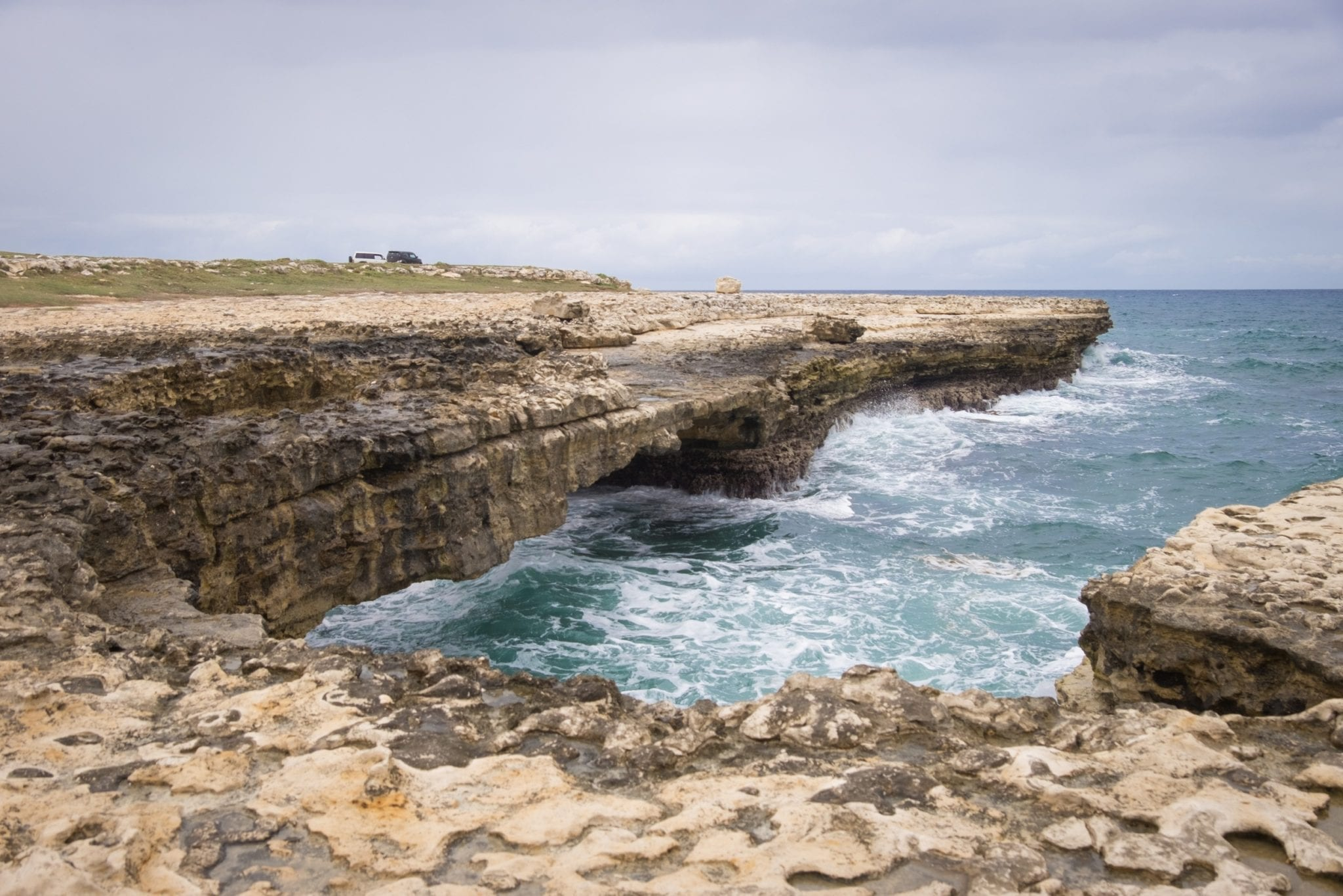 The Devil's Bridge, a rocky formation jutting out into the violent sea in Antigua. Waves are coming high, the sea and sky are both slate gray.