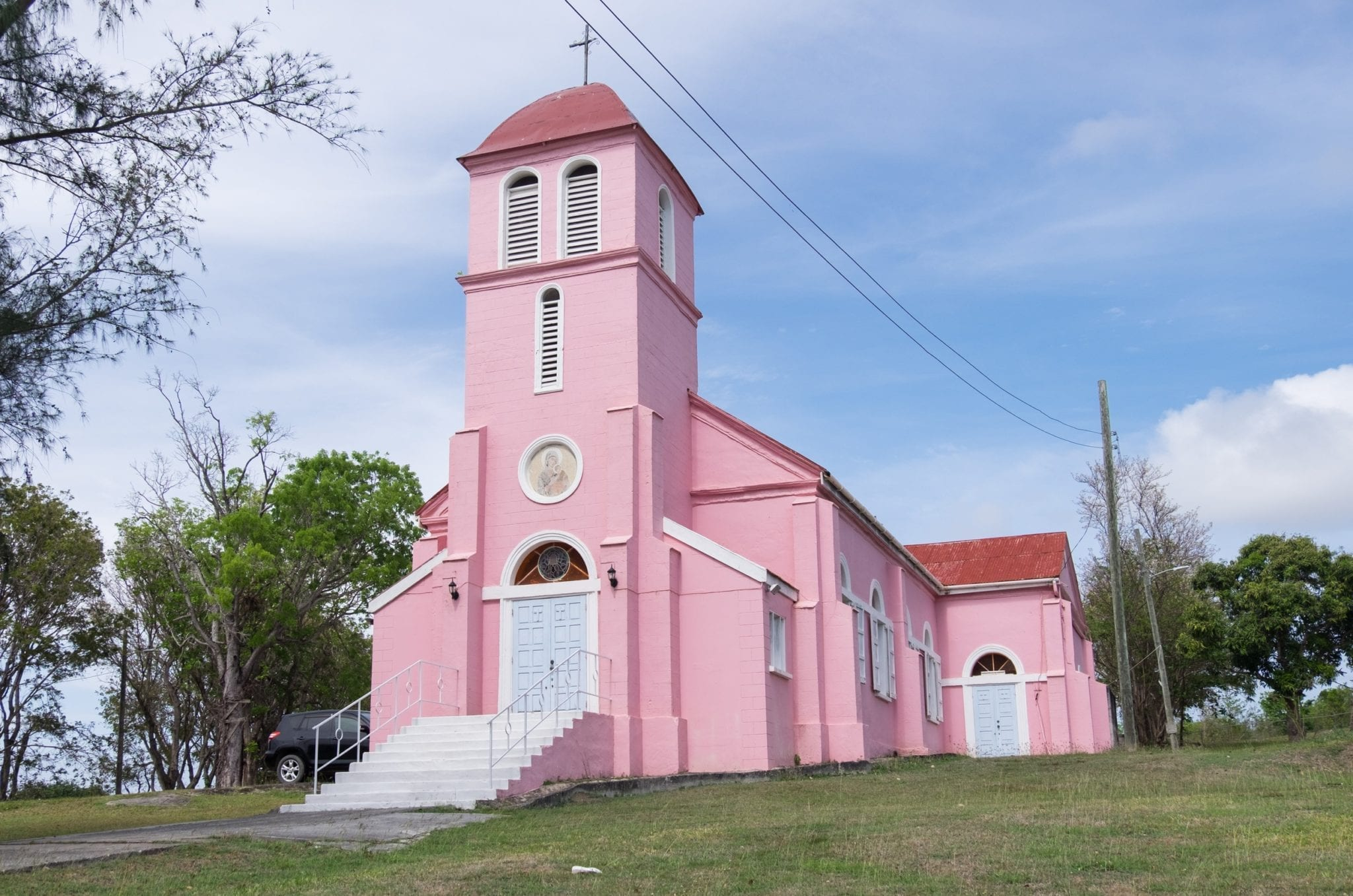 A small pink church is perched on a hill in Antigua with a soft blue and white sky in the background.