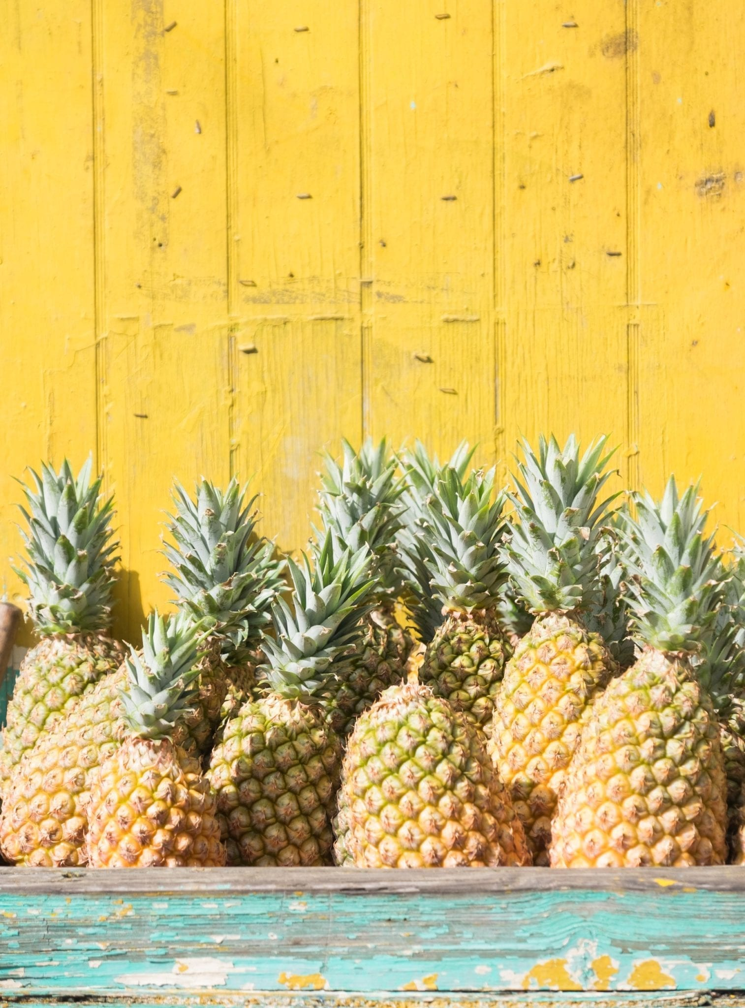 Several pineapples piled up on top of each other in a weathered turquoise wooden container in front of a yellow clapboard wall.