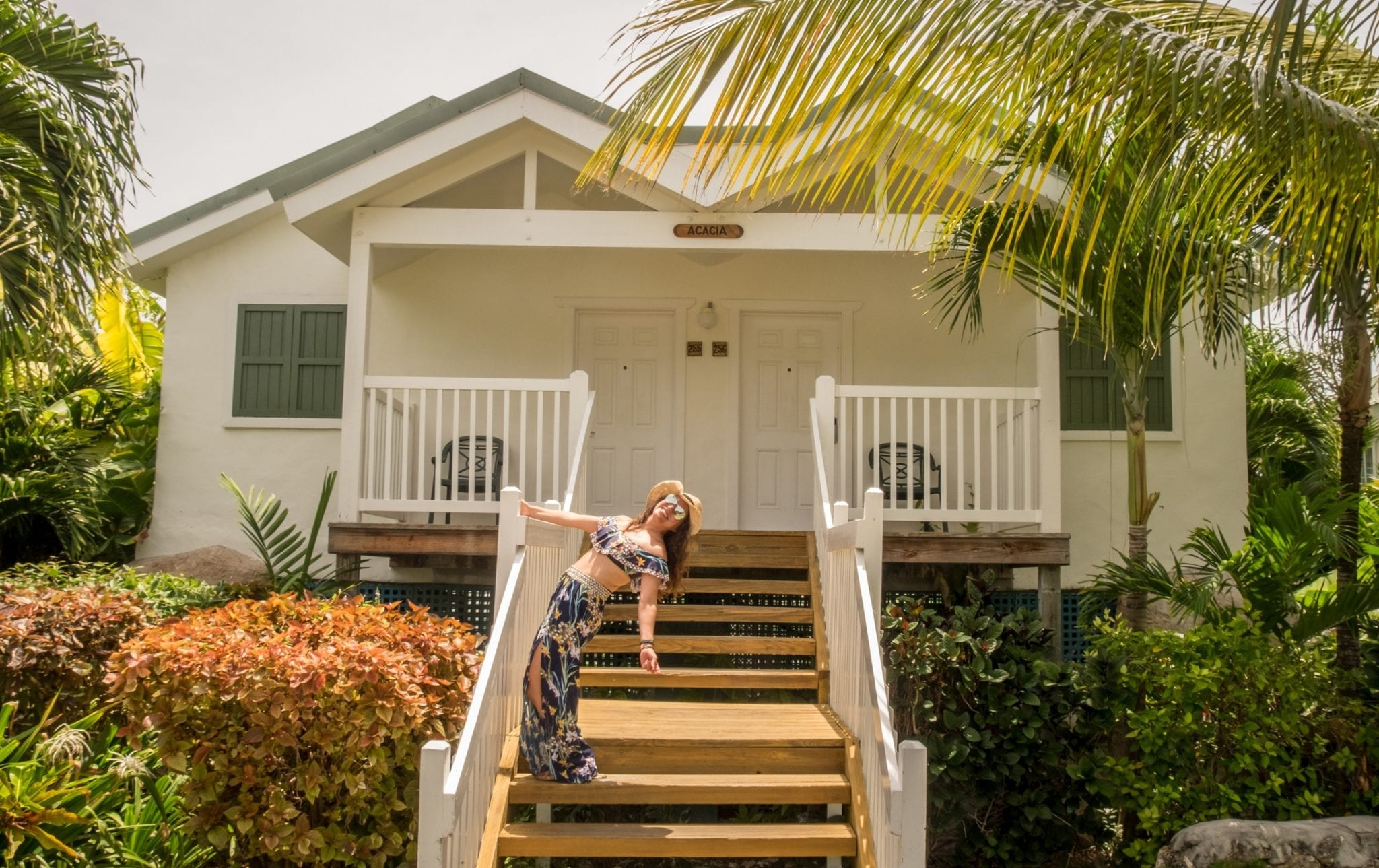 Kate posing in front of a cottage on the stairs leading up. The cottage has two doors in front and several palm trees around. Kate is holding onto the railing and arching her back so she's falling backward. She wears a straw hat, aviators, and a tropical-patterned bathing suit top that matches her genie-style pants.
