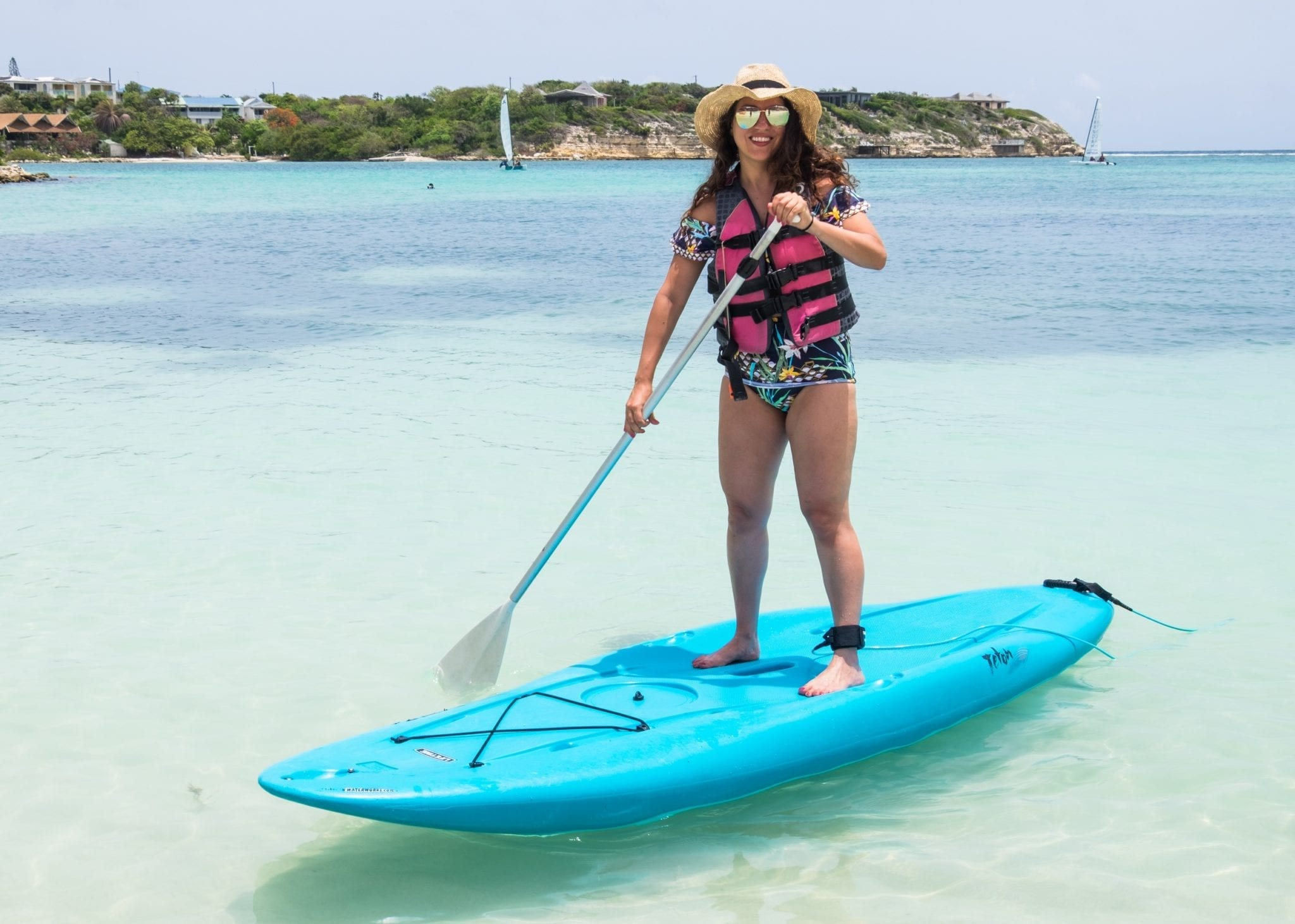 Kate paddles herself on a stand-up paddle board over turquoise water in Antigua. The board is bright blue and she wears a life vest over a bathing suit with a straw hat and aviator sunglasses.