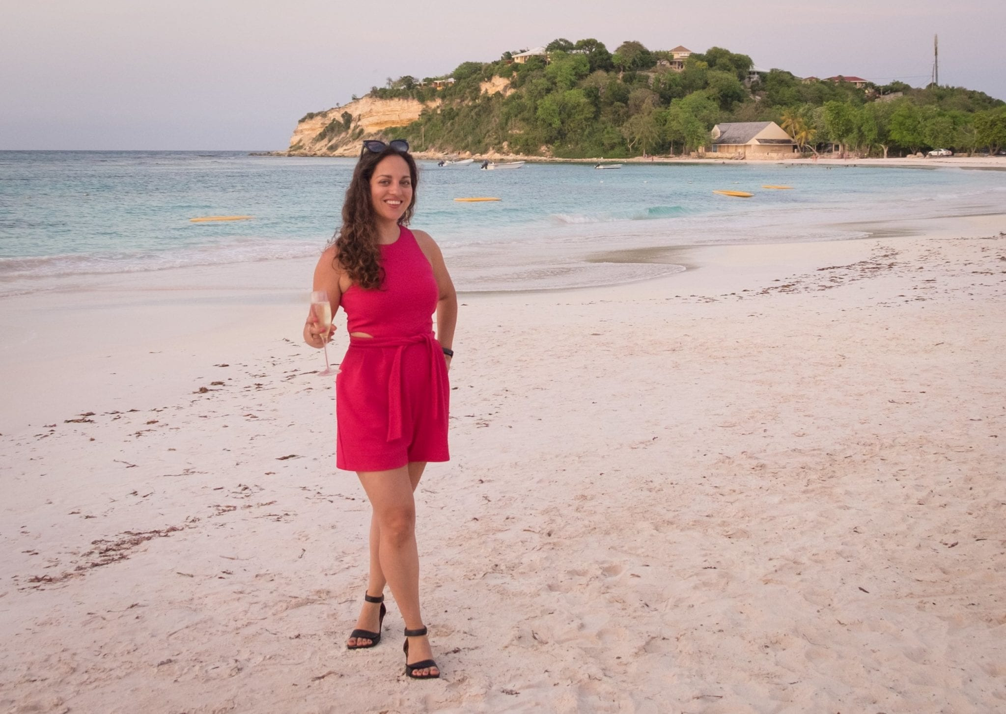 Kate wearing a hot pink romper and holding a glass of champagne, standing on a pinkish-white beach at sunset.