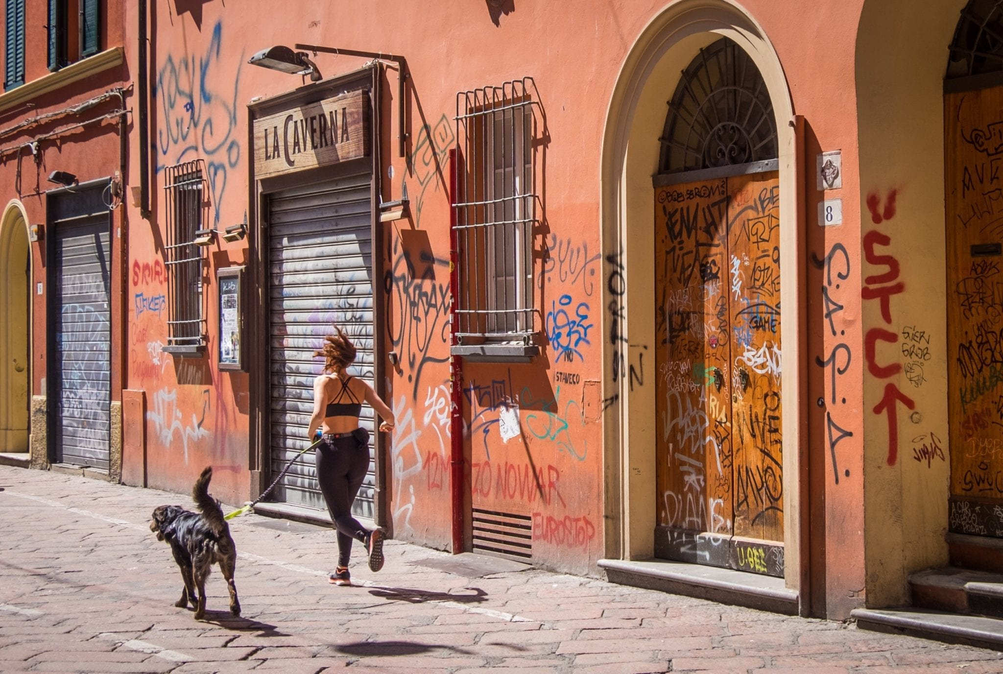 A woman in workout gear runs with her black medium-sized dog on a leash. They run past a pinkish-red wall covered with graffiti in Bologna, Italy.