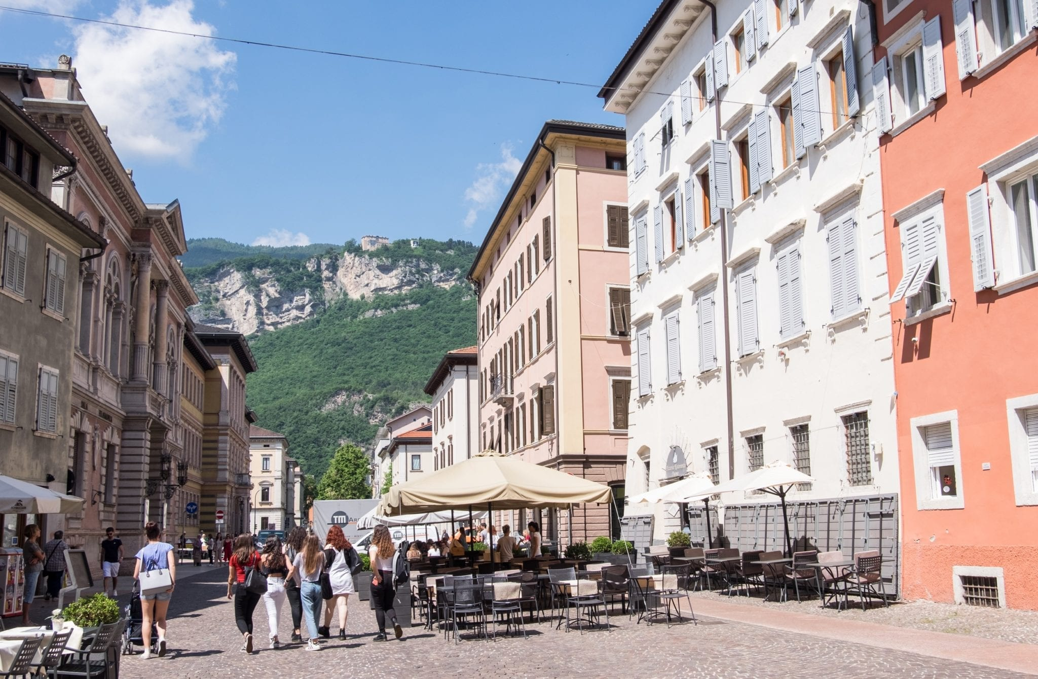 A piazza in Trento, Italy, gives way to green mountains in the background. The buildings are cream, white, and pale orange and a group of women walks together in the foreground.