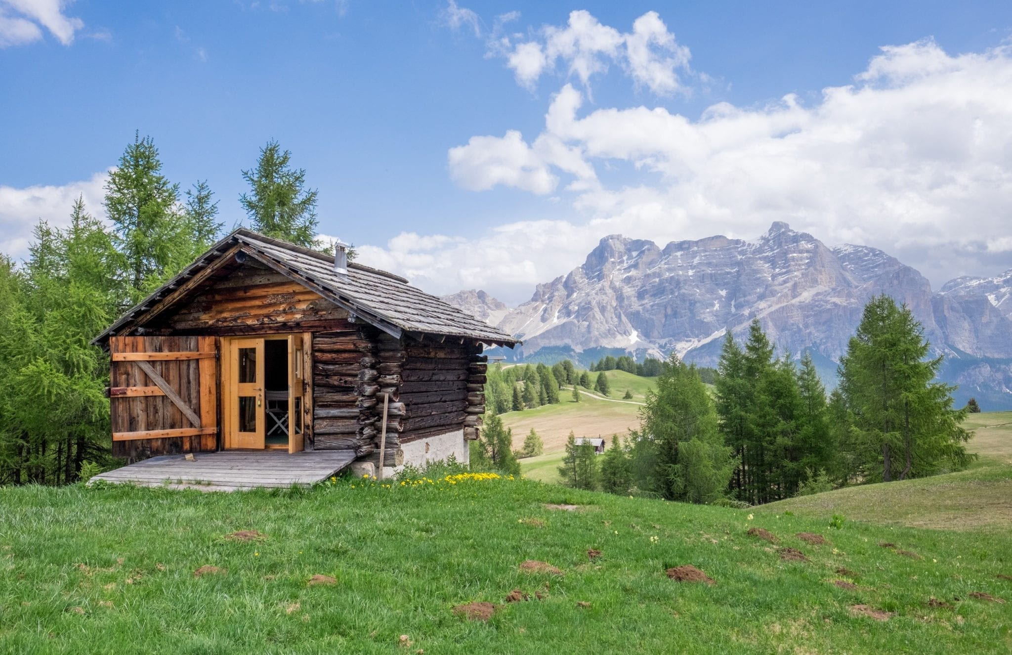Scene from Alto Adige (South Tyrol), Italy: A wooden mountain hut, looking like a cabin, is on the left side of the screen, perched on grass; in the background, blue mountains rise up beneath a blue sky streaked with white clouds.