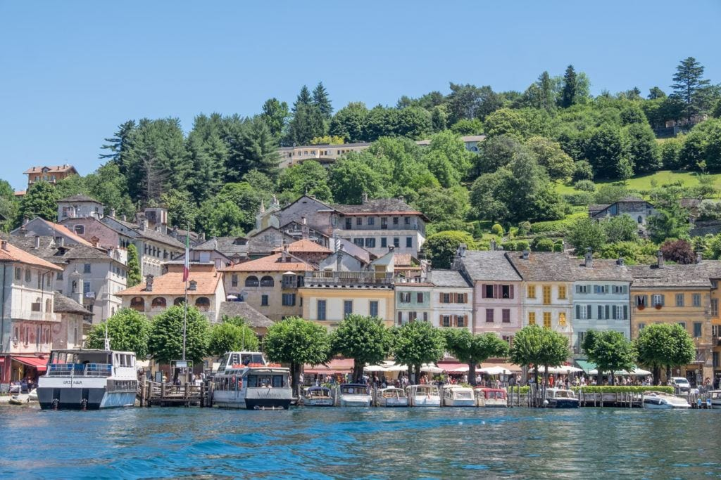 Pastel-colored houses are sitting right on Lake Orta, with boats in front of them in the water. A large green hill rises behind them underneath a bright blue sky.