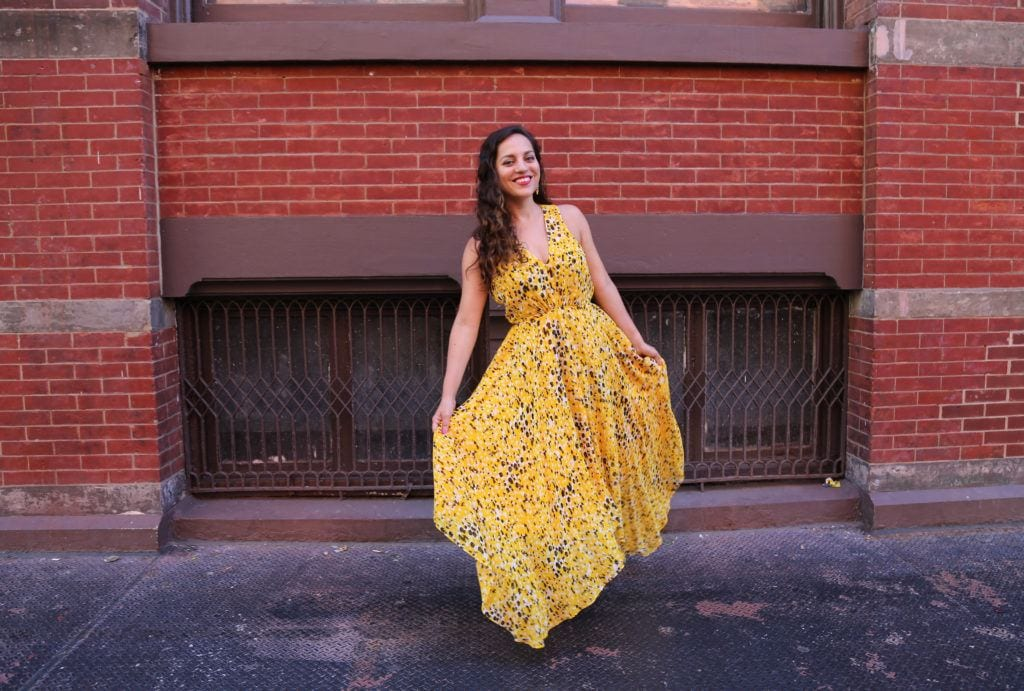 Kate wearing a big yellow gown in front of a brick wall in SoHo, NYC.