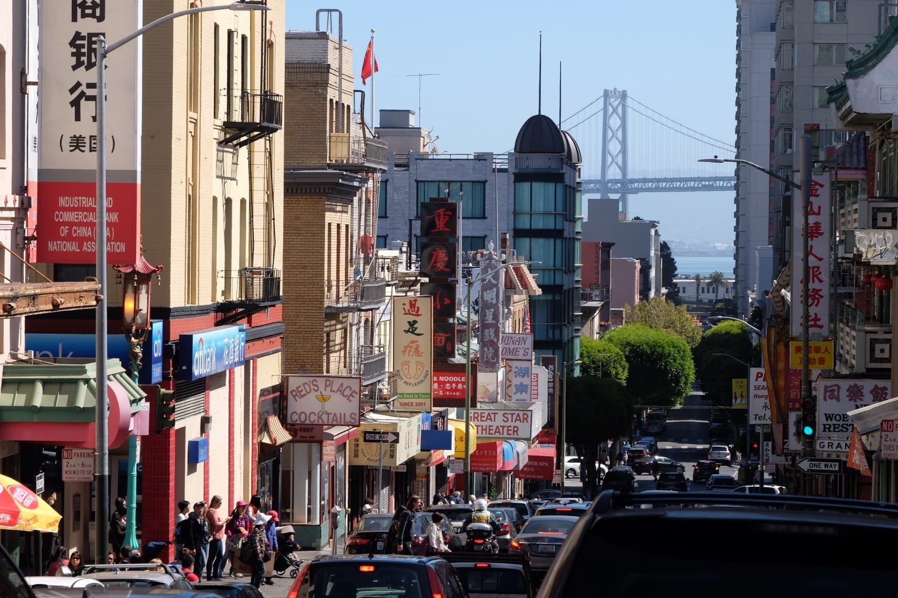 View over Chinatown in San Francisco, lots of store signs jutting out at angles, leading to a bridge underneath a blue sky.