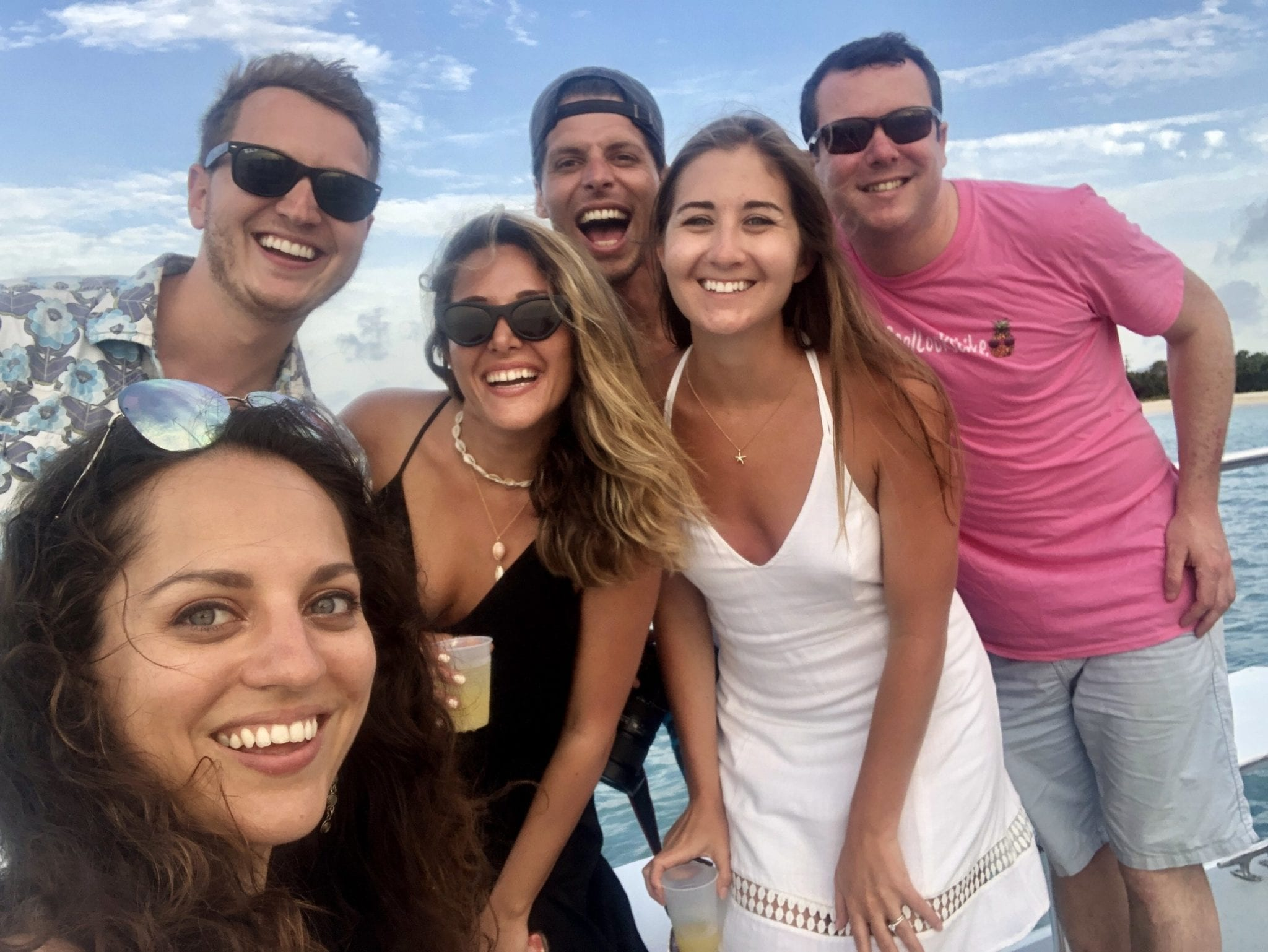 Kate and a group of several friends posing and smiling on a catamaran in Antigua