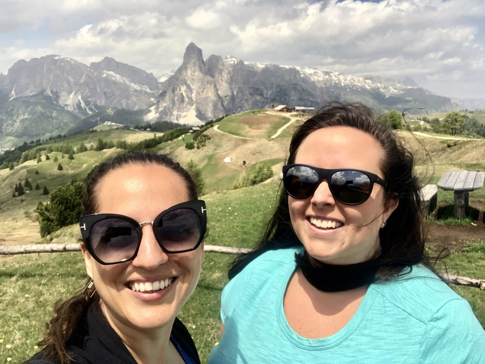 Kate and Cailin take a selfie wearing sunglasses in the Italian Dolomites. Behind them is a row of jagged mountains in the distance. There is a dramatic cloudy sky.