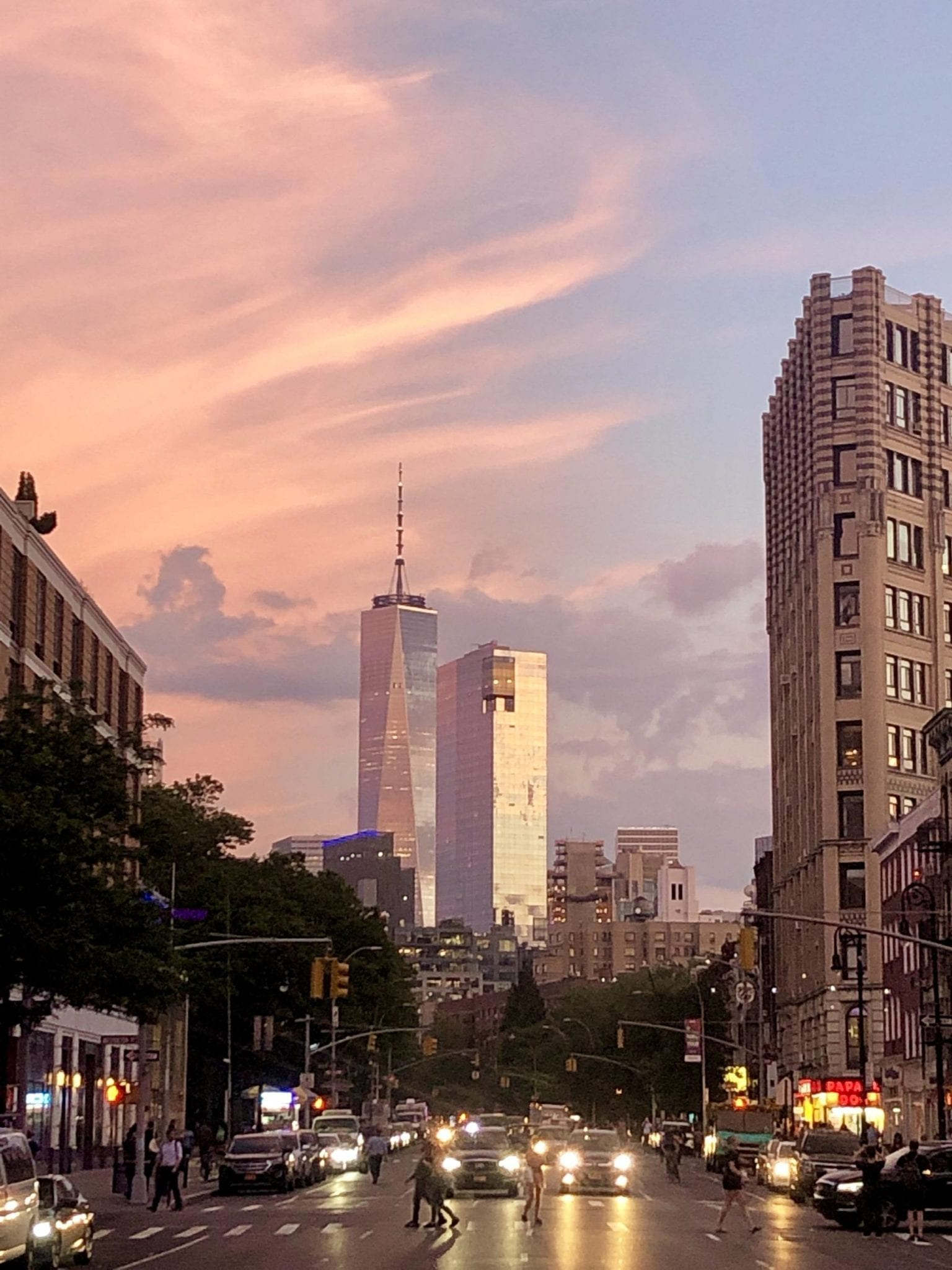 The One World Trade Center building in New York is illuminated by a pink and blue sunset streaked with clouds. The view is facing straight down Sixth Avenue and there are a few sets of headlights facing the camera.