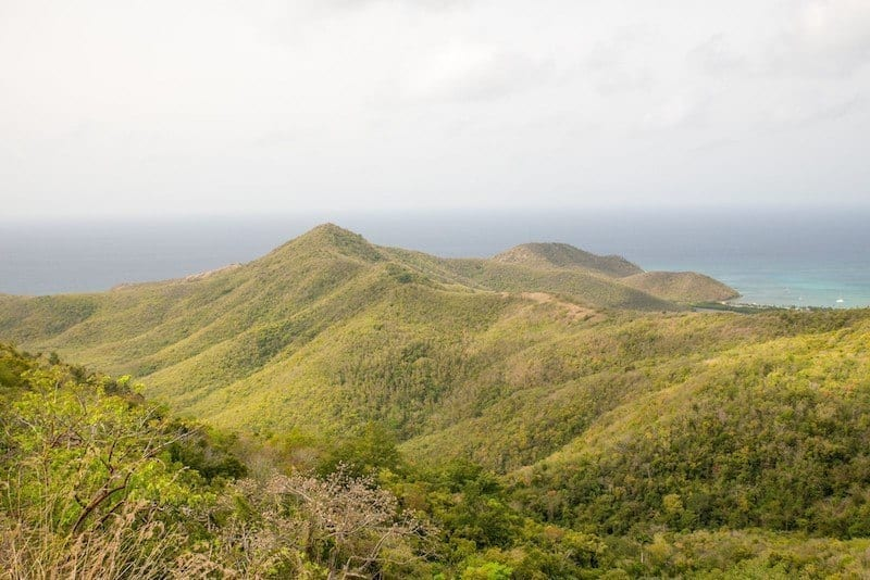 Signal Hill in Antigua -- several green pointy hills in front of a blue-gray ocean horizon.