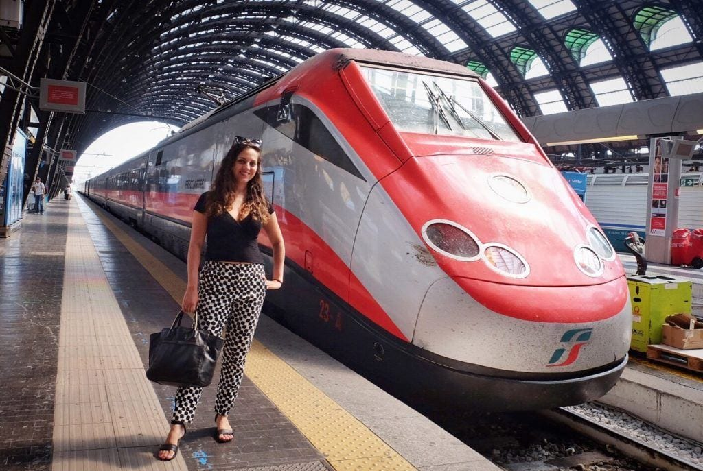 Kate stands wearing a black shirt and black and white patterned pants, holding a black purse, in front of a modern Frecciarossa train at Milan train station. The train is sleek and is silver and red with a long angled nose in front.