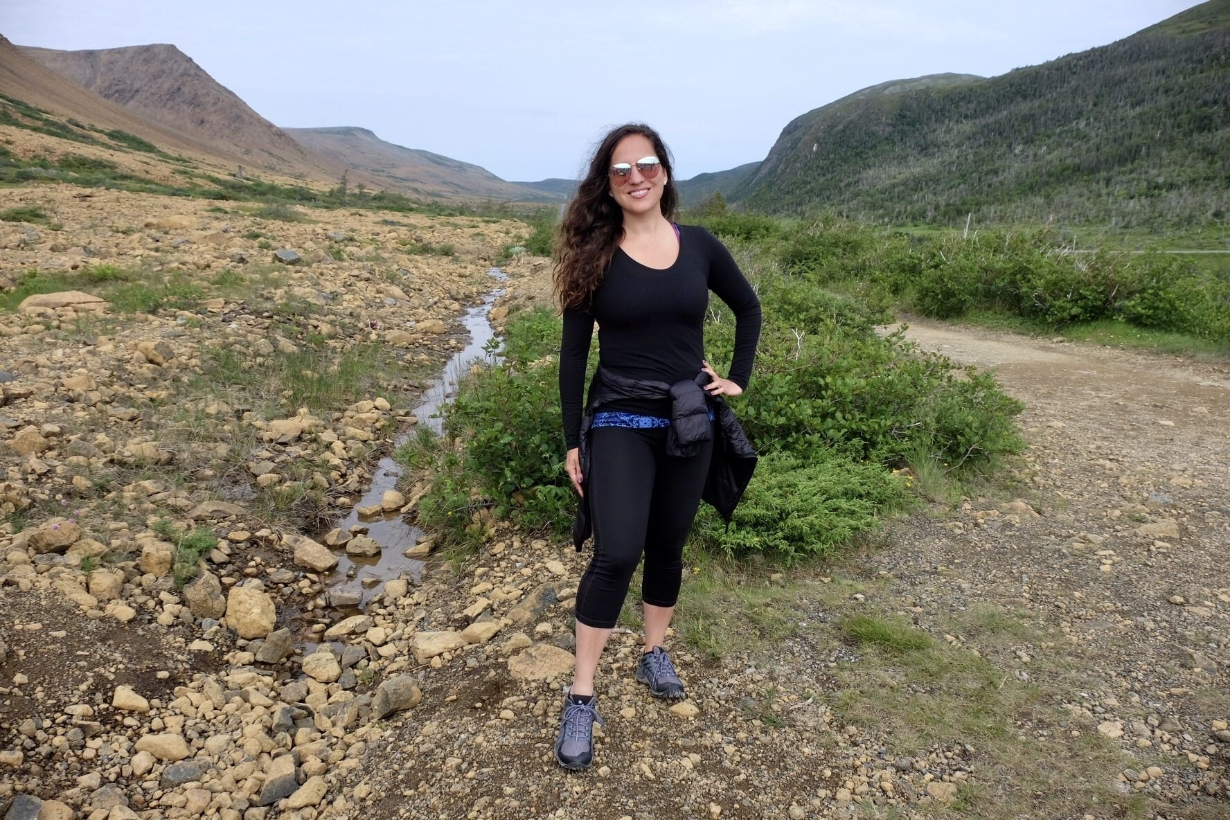 Kate stands in the Tablelands of Newfoundland surrounded by orange rocks and grassy hills.