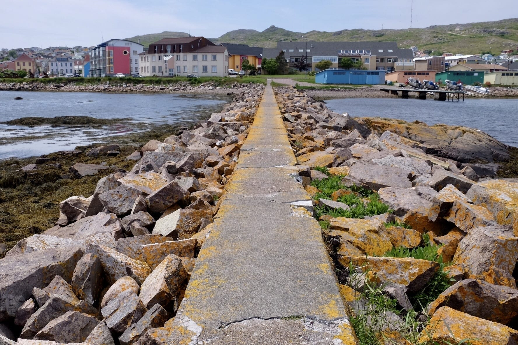A concrete path with rocks piled on each side leads to the colorful houses of St. Pierre and Miquelon.