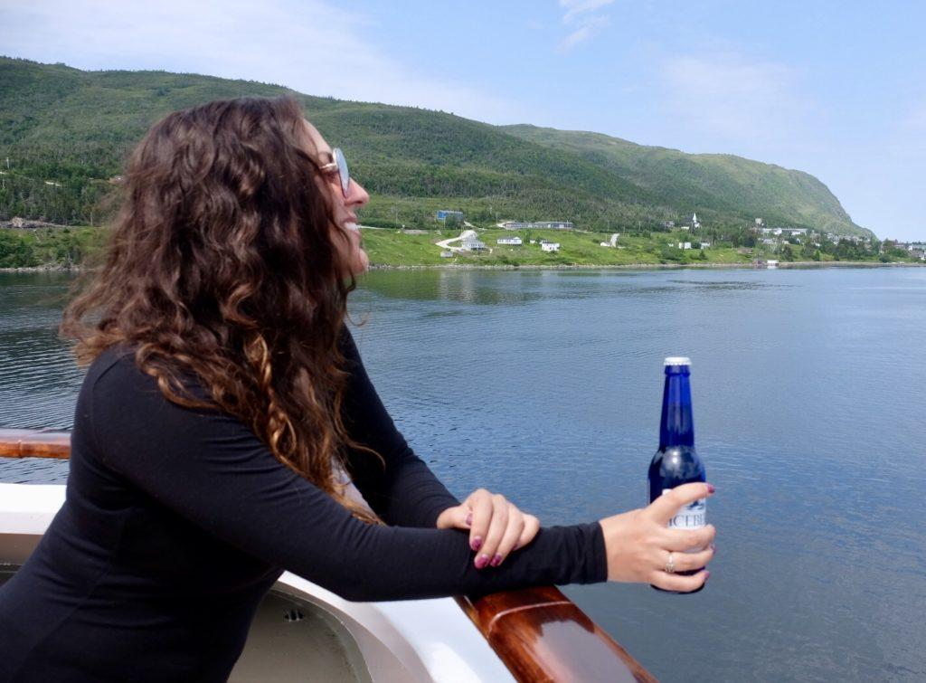 Kate leans over the edge of a ship, holding a cobalt blue Iceberg Beer bottle in her hand and looking over the glassy bright blue Bonne Bay in Newfoundland.