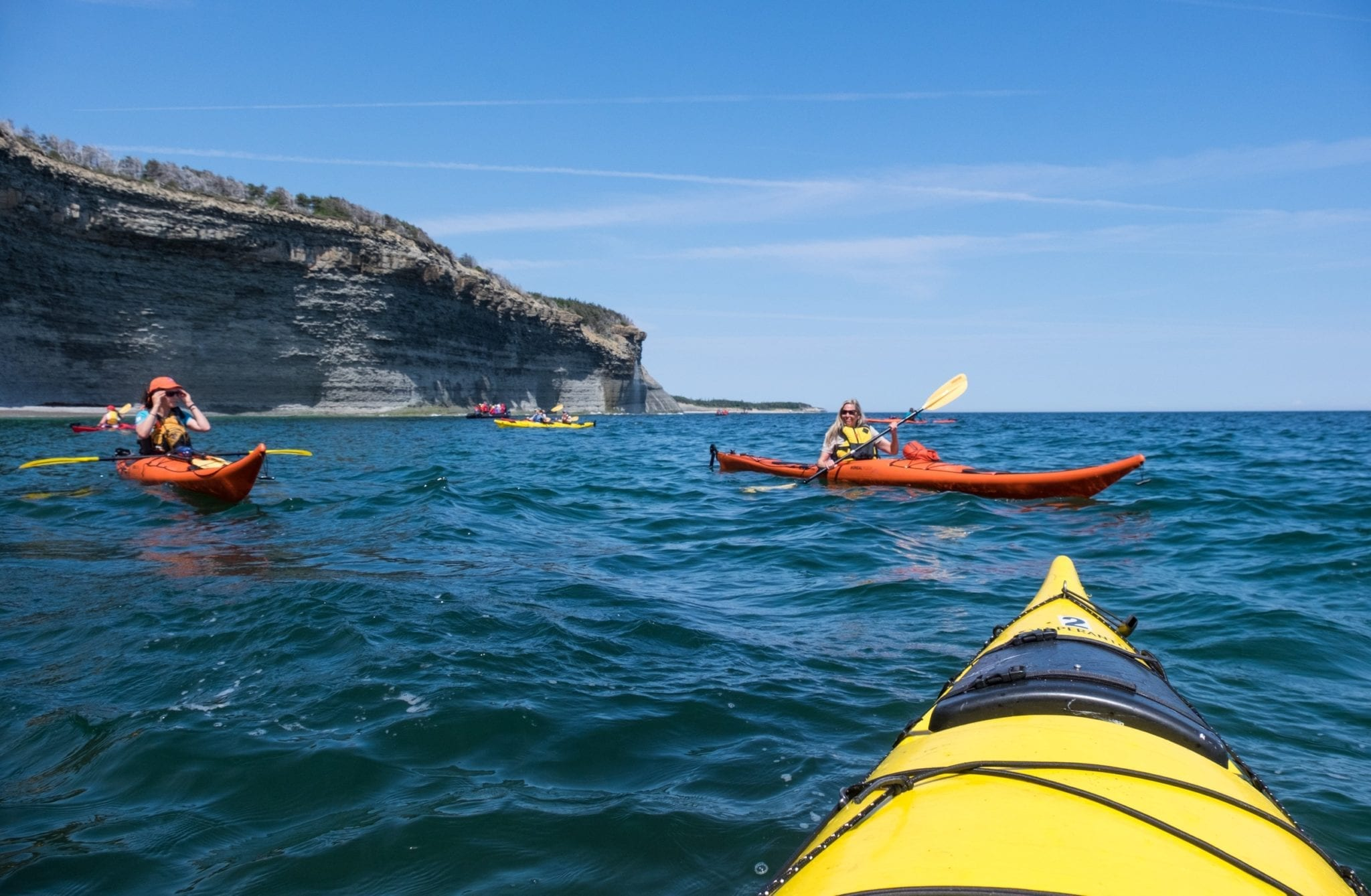 Shot from the front of a yellow kayak, you see several kayakers in bright blue water and cliffs in the background.