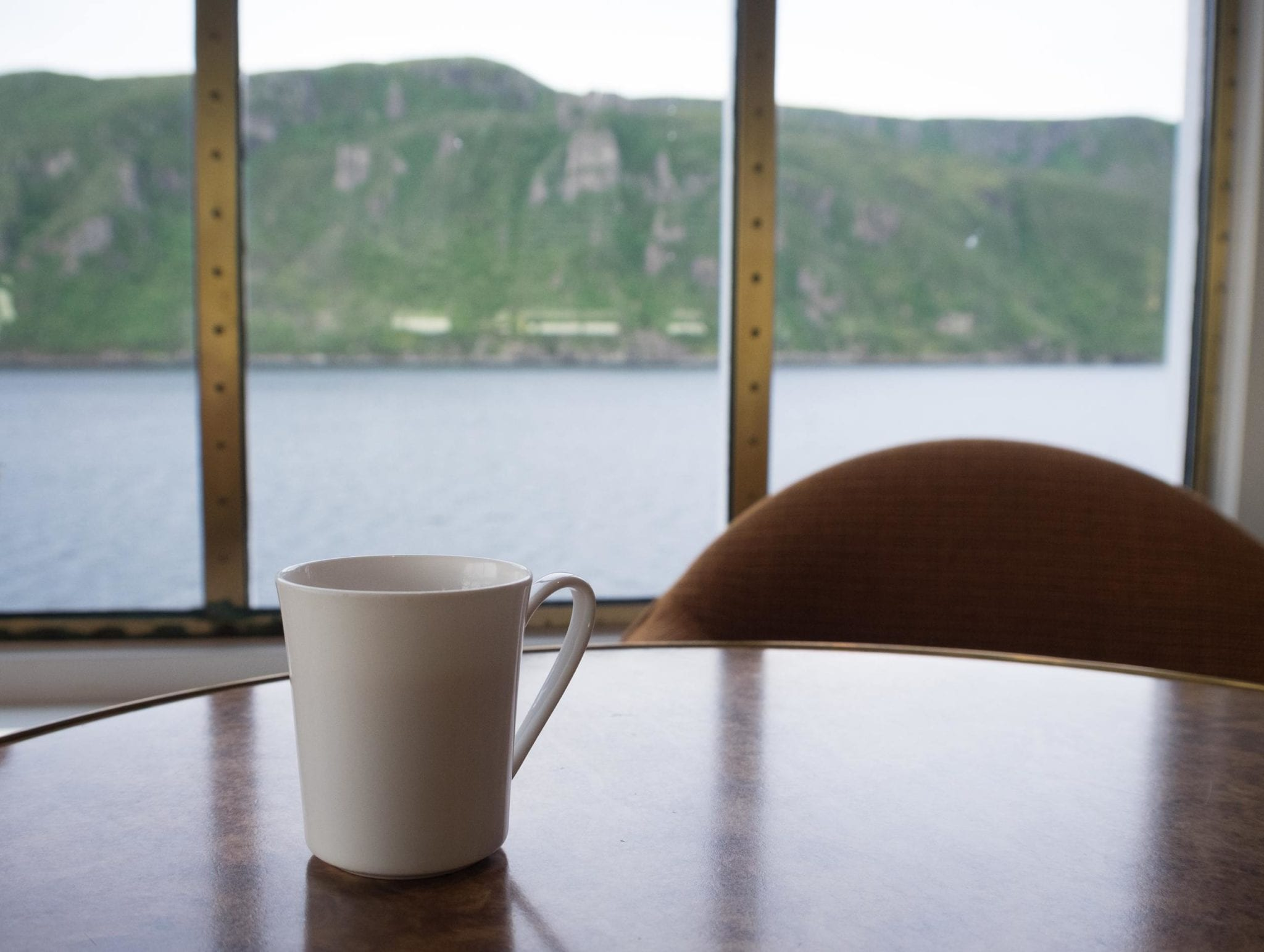 A cup of tea sits on a table in front of windows revealing the fjord at Bonne Bay, Newfoundland.