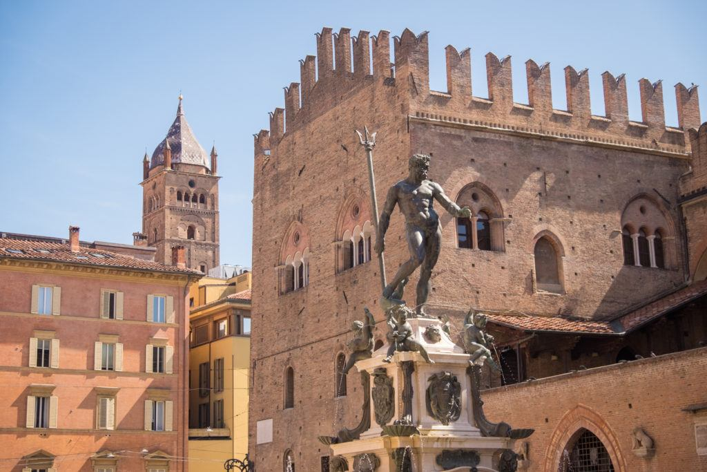 In Piazza Maggiore in Bologna, the statue of Neptune gesticulates as if he's about to kick something. Behind him are rose-colored brick buildings.