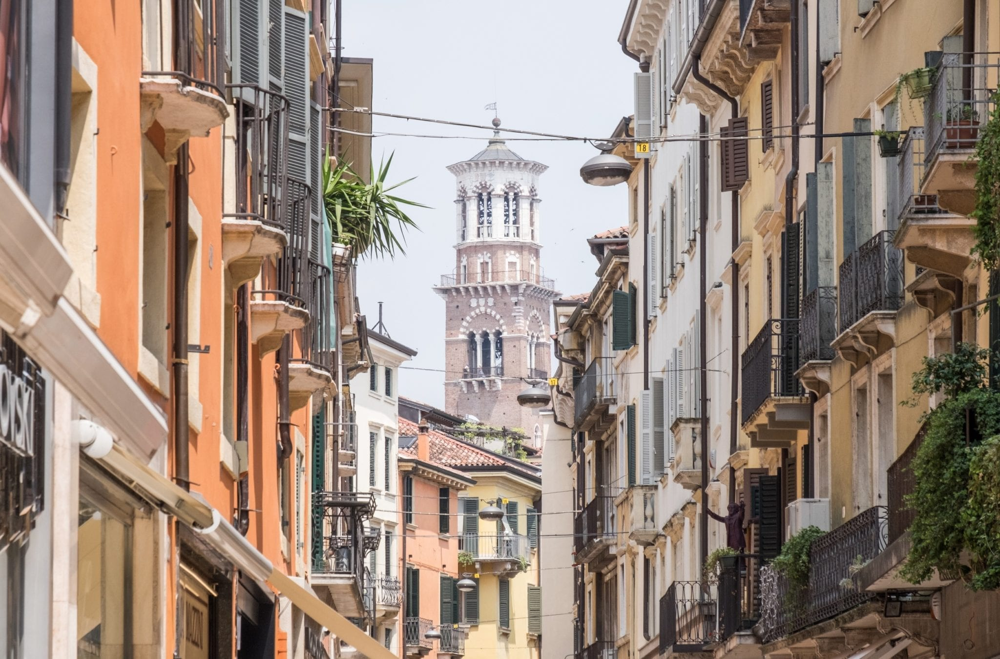 In Verona, you see the tower of a church rising in between residential buildings painted gold and yellow.