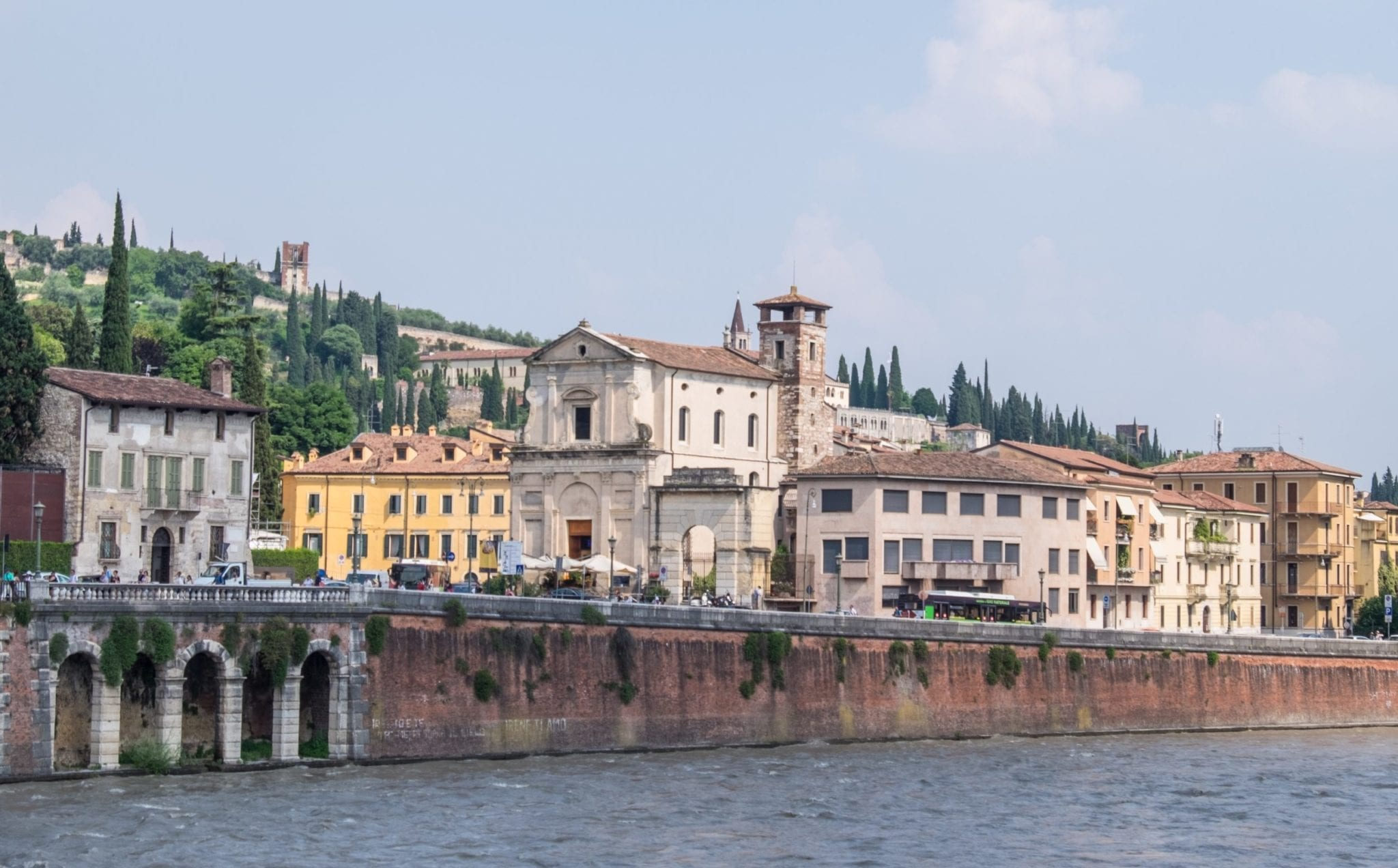 The riverbank in Verona, Italy, with cream-colored buildings and tall cypress trees.