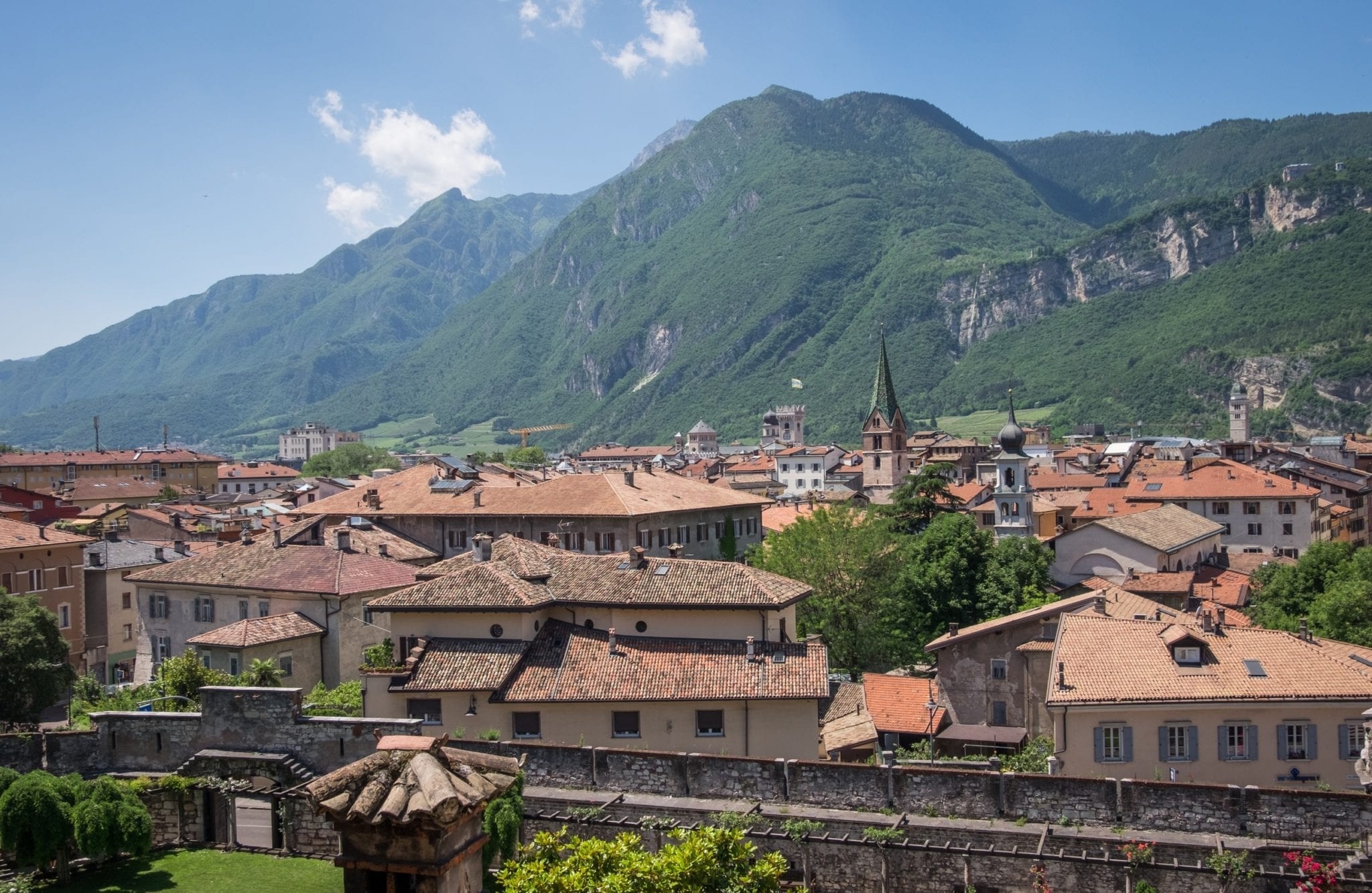 A view of the terra cotta roofs in the old town of Trento, Italy, with green mountains in the background underneath a blue sky with white spotted clouds.