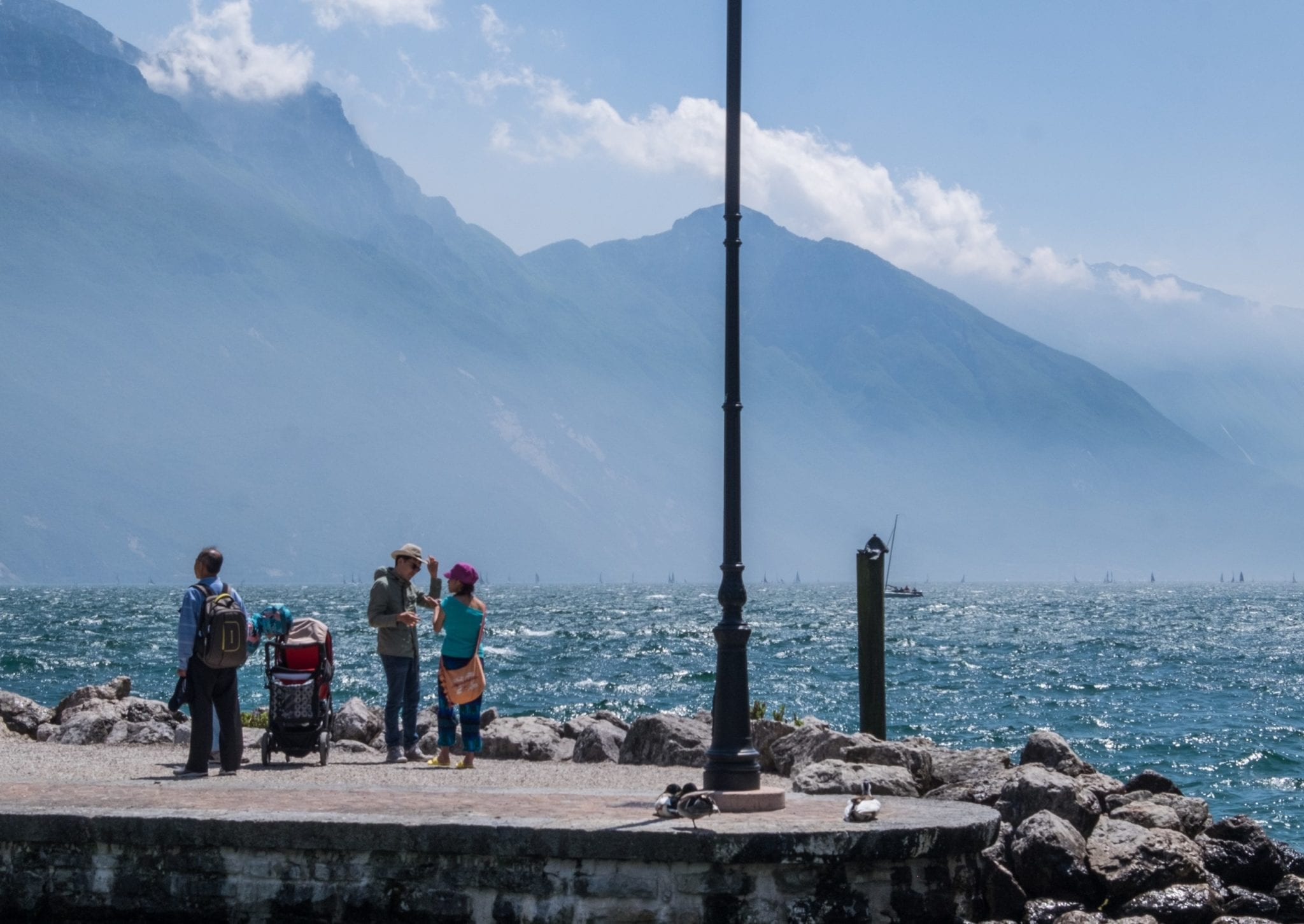 Four adults and a baby carriage stand on a jetty jutting out into the blue Lake Garda, where a windy day is stirring up white caps in the waves. The mountains are jagged in the background and seem to be falling into the lake.