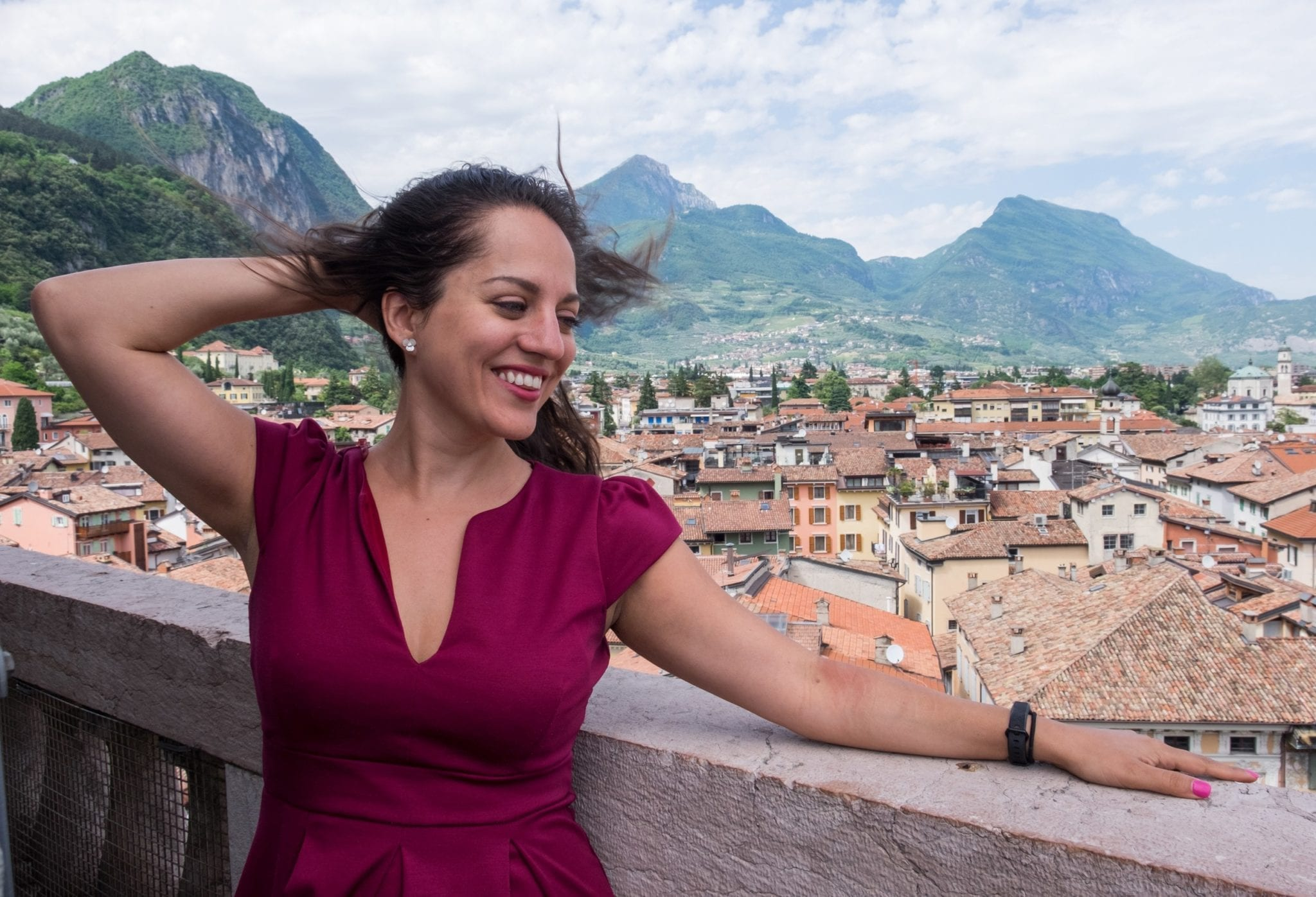 Kate smiles with her hand behind her head and wears a red dress and stands on top of a tower in Riva del Garda, Italy, overlooking terra cotta roofs, pastel buildings, with jagged mountains and a white and blue streaked sky in the background.