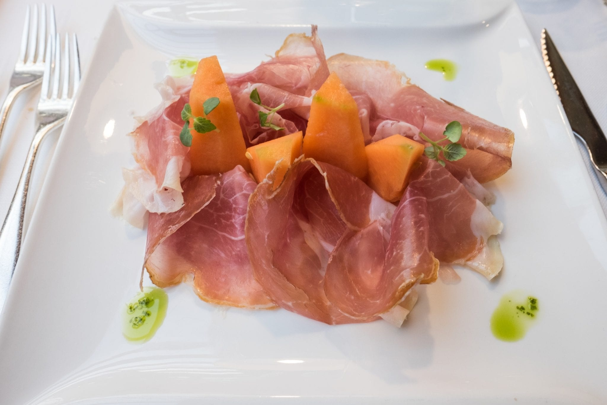A plate of pillowy pink speck, or Tyrolean ham, with pieces of orange melon.