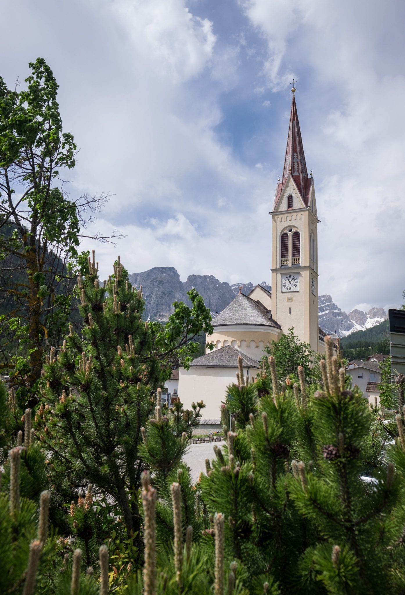 A church steeple pokes out of an Italian mountain landscape in the Dolomites. The church is surrounded by forest.