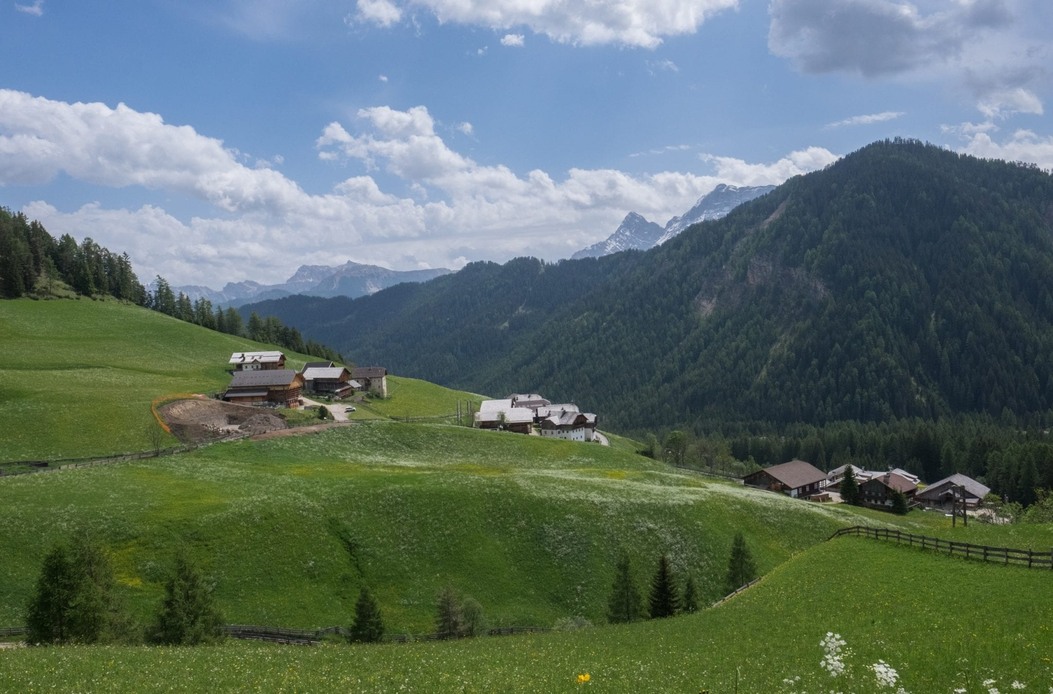 A view of the Dolomites with mountains in the distance and tiny Alpine huts on green hills in the foreground.