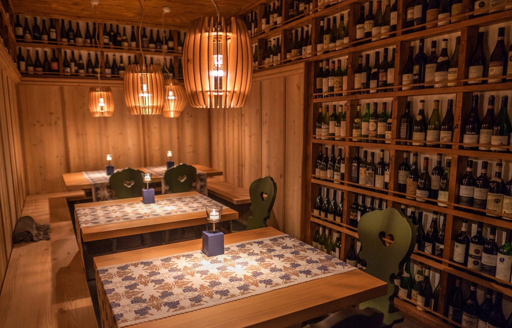A wine cellar with bottles lining the wood-paneled walls and wooden seats covered with patterned tablecloths.