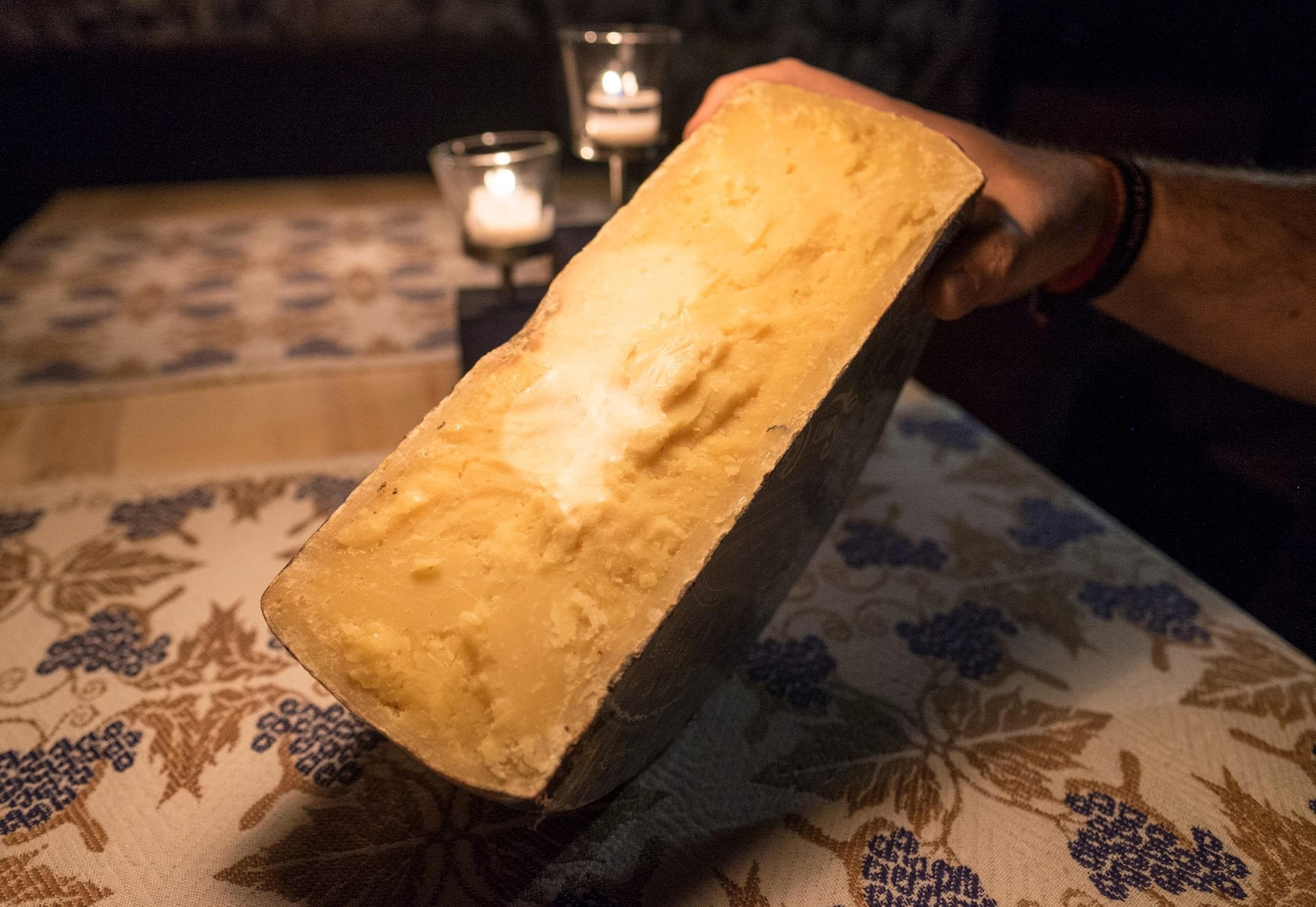A giant chunk of cheese being held up in the dim light of the wine cellar.
